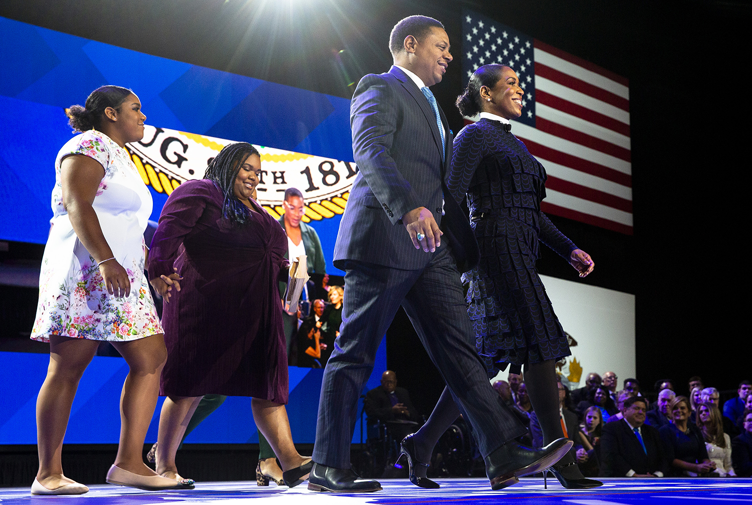 Lt. Gov.-elect Juliana Stratton, accompanied by her fiancé, Bryan Echols and her daughters, Ryan, Tyler and Cassidy, not seen, walks onto the stage to take the oath of office during the Illinois Inaugural Ceremony Monday, Jan. 14, 2019 a the Bank of Springfield Center in Springfield, Ill. [Rich Saal/The State Journal-Register]