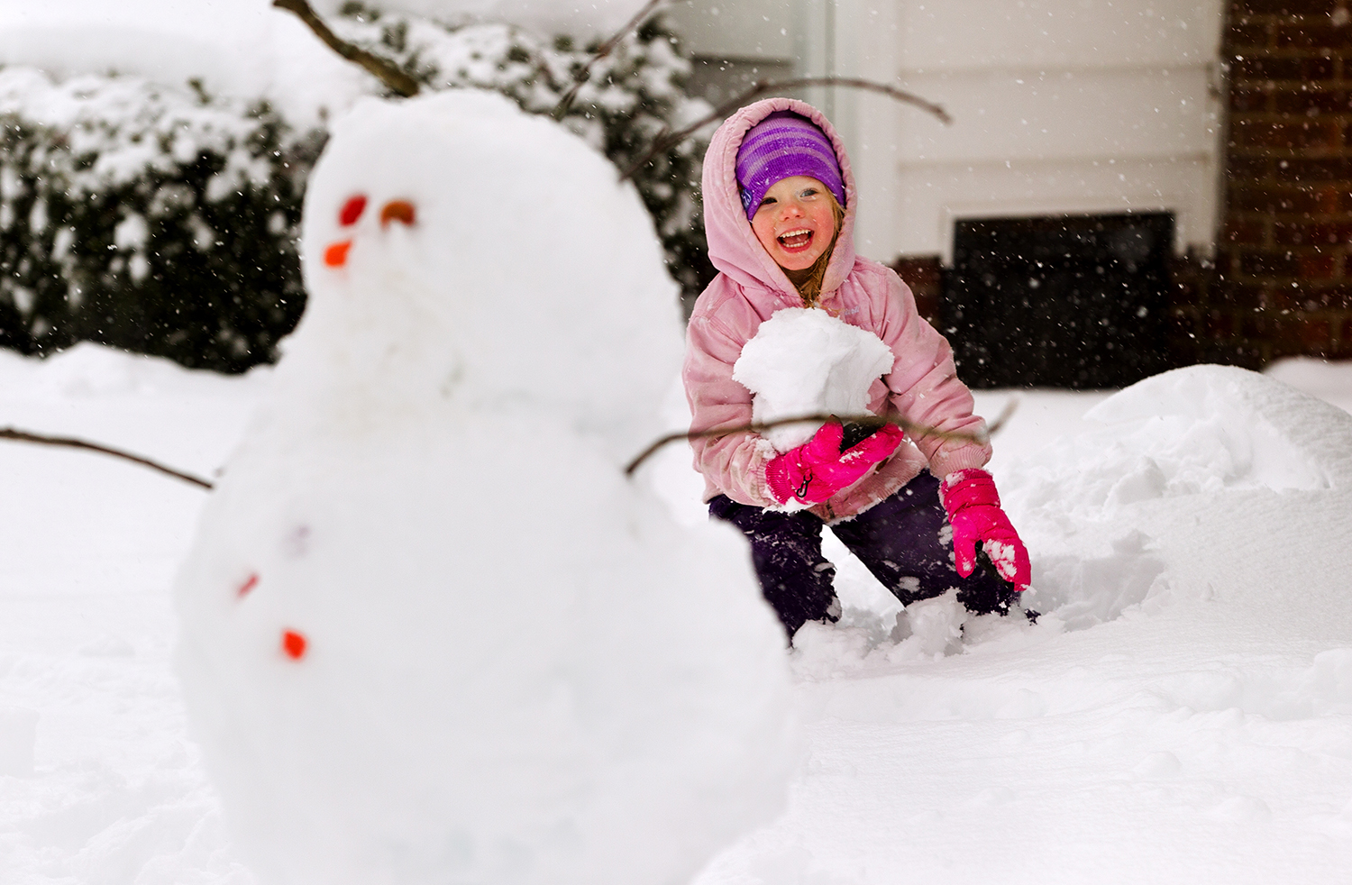 Eleanor Orzechowski laughs as she gathers an armful of snow in her front yard Saturday, Jan. 12, 2019. Her family had cleared the driveway, made a snowman and was working on a snow wall with some of the more than 10 inches of snow that had fallen by noon. [Ted Schurter/The State Journal-Register]