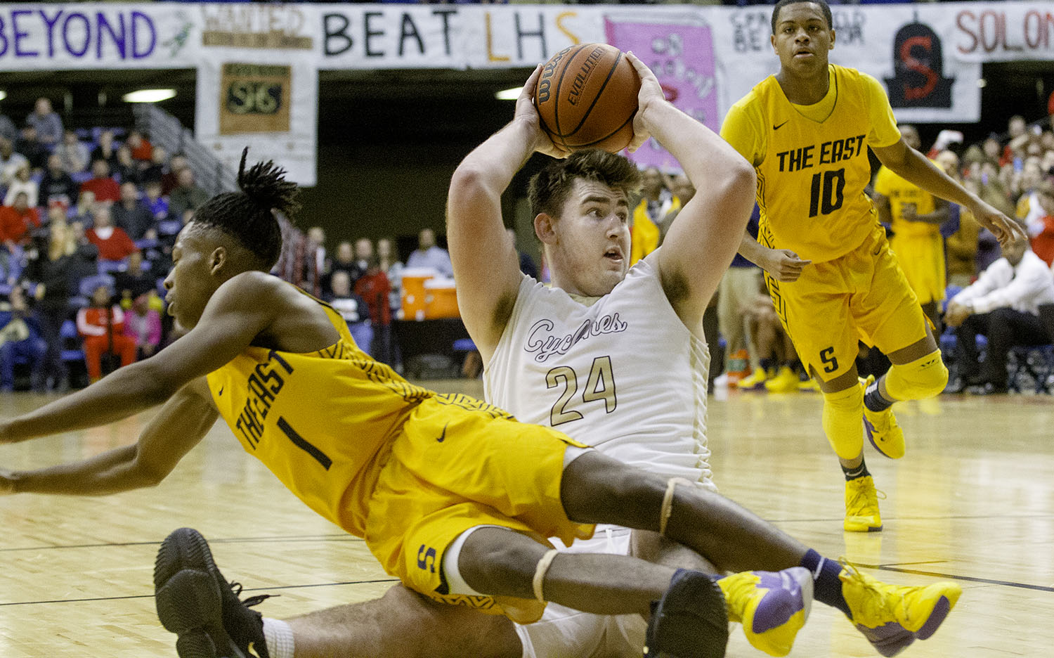 Sacred Heart-Griffin's Nick Broeker passes the ball after grabbing it off the floor as Southeast's Stepheon Sims dives over him during the Boys City Tournament at the Bank of Springfield Center Friday, Jan. 18, 2019.  [Ted Schurter/The State Journal-Register]