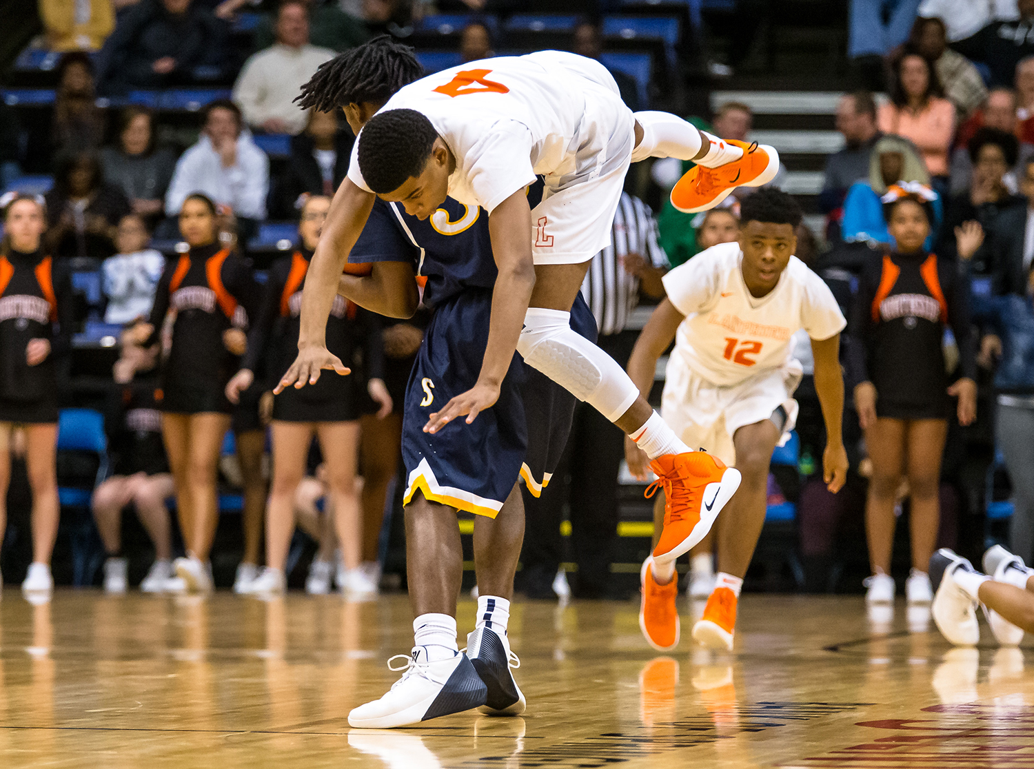Lanphier's Larry Hemingway (4) flies over Southeast's Stepheon Sims (32) as he stops in his tracks in the first quarter on opening night of the Boys City Tournament at the Bank of Springfield Center, Wednesday, Jan. 16, 2019, in Springfield, Ill. [Justin L. Fowler/The State Journal-Register]