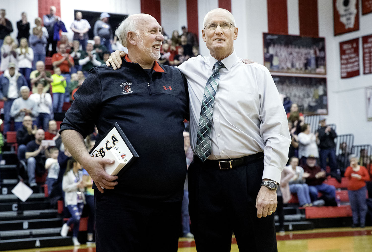 Nokomis High School boys basketball head coach Steve Kimbro, left, stands with former teammate and Lincoln High School boys basketball head coach Neil Alexander during a special ceremony to honor Kimbro's recent entrance into the 800 win club before the two schools competed Saturday, Jan. 26, 2019. Alexander has also earned 800 wins as a coach. [Ted Schurter/The State Journal-Register]