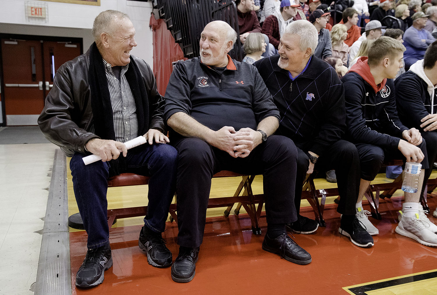 Loren Wallace, the former Nokomis head coach and Hall of Fame member, surprises his former player and current head coach Steve Kimbro as he sits down beside him at the start of the junior varsity game Saturday, Jan. 26, 2019. John Flowers, Kimbro's former teammate, is at right. [Ted Schurter/The State Journal-Register]