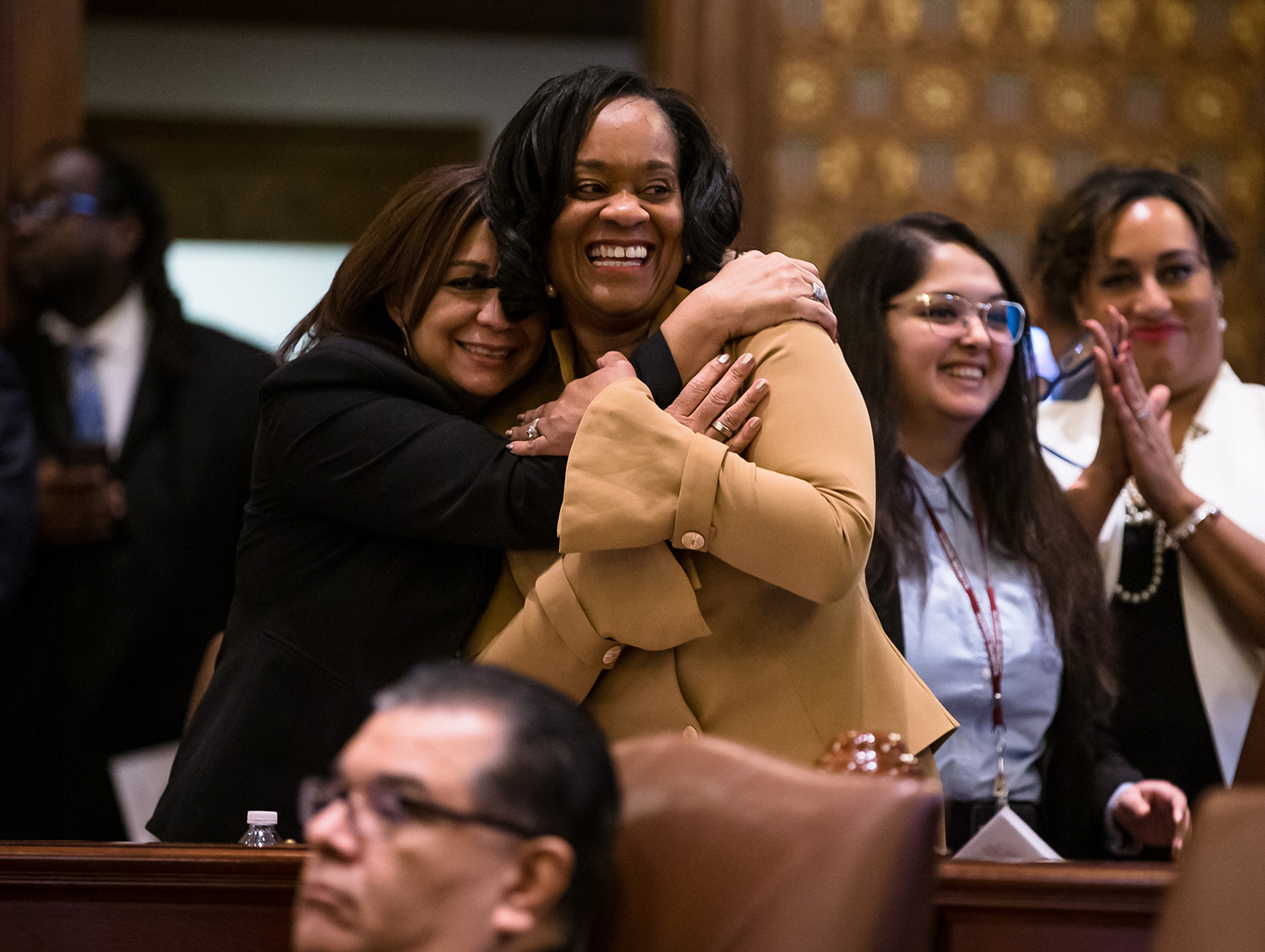 Illinois State Sen. Kimberly Lightford, D-Maywood, center, gets a hug from Illinois State Sen. Iris Martinez, D-Chicago, left, after Senate Bill 1, a bill sponsored by Lightford to raise the state's minimum wage to $15 an hour by 2025, passed the Senate on a vote of 39-18 at the Illinois State Capitol, Thursday, Feb. 7, 2019, in Springfield, Ill. [Justin L. Fowler/The State Journal-Register]