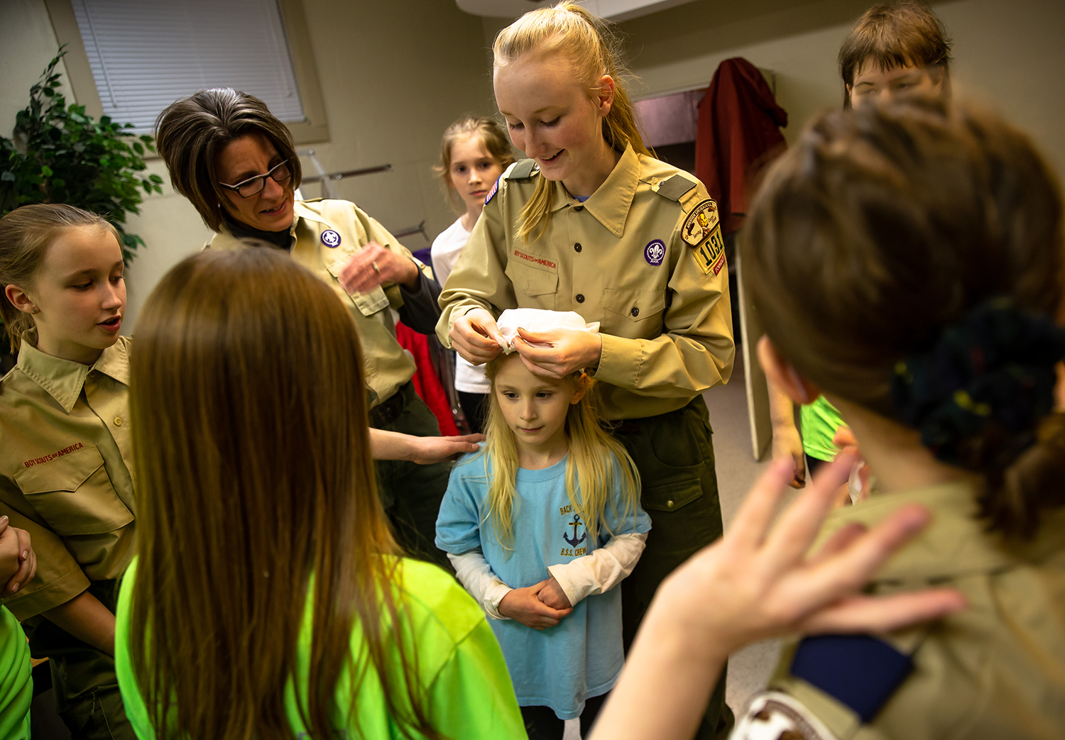 Scout Arianna Antonacci, 13, uses Josie Kren, 6, as a test subject to learn how to make a bandage out of a piece of cloth with the assistance of Scoutmaster Jennifer Wente, left, as the girls prepare for the First Aid Meet during a meeting of Scouts BSA Troop 1031 at the Blessed Sacrament Church, Monday, Feb. 11, 2019, in Springfield, Ill. Troop 1031 is among the first three all-female troops in the Springfield area to receive their charters Feb. 1 through Boy Scouts of America. [Justin L. Fowler/The State Journal-Register]