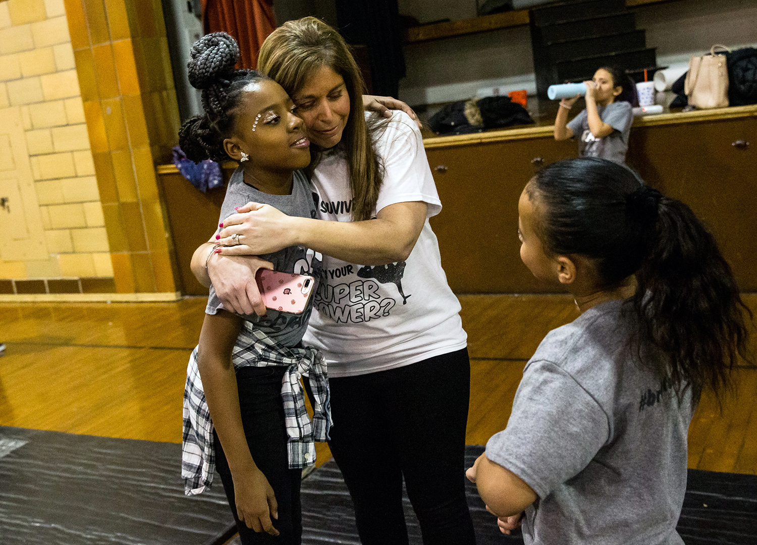 Kim Drewes, a third grade teacher at Dubois Elementary School and the hip hop dance team instructor, gets a hug a from Shyahnna Purnell after the team practiced their routine before performing during halftime of a junior varsity basketball game at Lanphier High School, Tuesday, Feb. 12, 2019, in Springfield, Ill. Drewes designed the choreography around her fight against a brain tumor in which she shared her experience with the kids and helped her through her battle.  [Justin L. Fowler/The State Journal-Register]