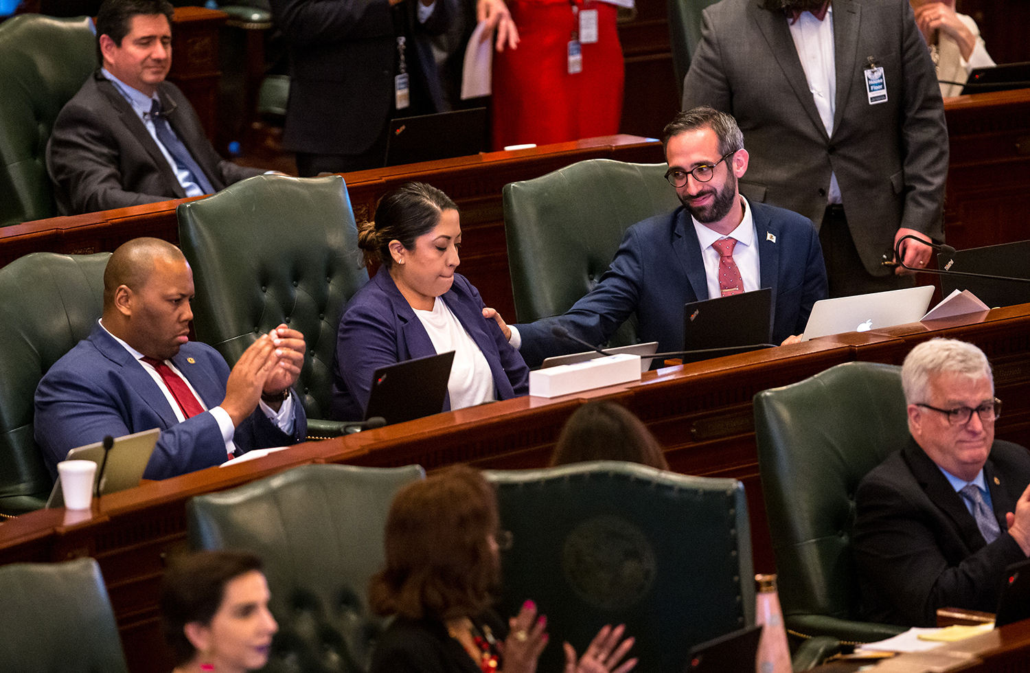 Illinois State Rep. Will Guzzardi, D-Chicago,, right, gives Illinois State Rep. Celina Villanueva, D-Chicago, a pat on the shoulder after she gave her remarks in support of Senate Bill 1, a bill to raise the minimum wage to $15 by 2025, citing the experience of her family working multiple jobs to get by during debate on the House floor at the Illinois State Capitol, Thursday, Feb. 14, 2019, in Springfield, Ill. [Justin L. Fowler/The State Journal-Register]