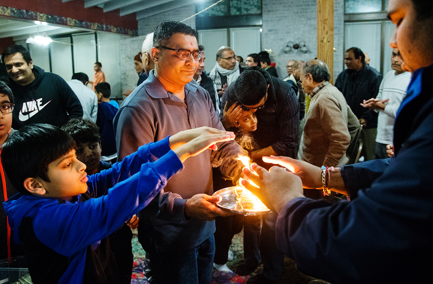Haresh Gajera carries a tray of burning wicks during the arti prayer at the conclusion of worship Sunday, Feb. 17, 2019. The tray is passed around to allow members to hover their down-turned hands over the flame and then touch them to their eyes and head to convey the purificatory blessing, previously conveyed from the Deities to the flame, to the devotee. [Ted Schurter/The State Journal-Register]