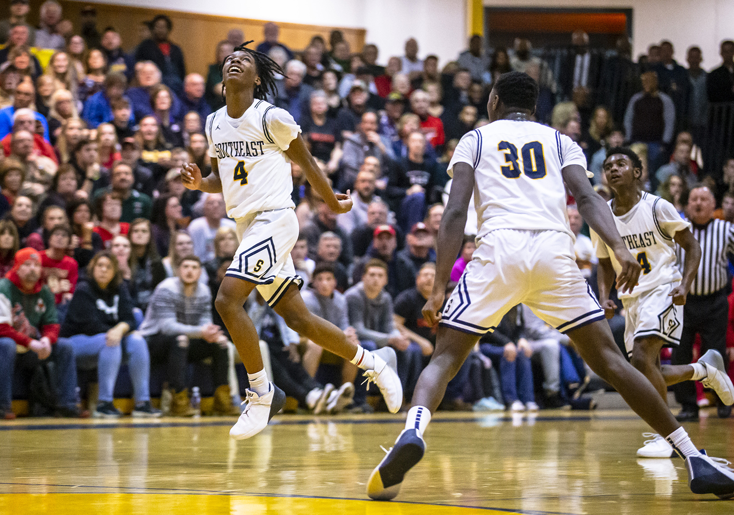 Southeast's Terrion Murdix (4) is all smiles as he runs off the court with his teammates with the Spartans heading into halftime with a commanding lead against Lincoln during the Boys Class 3A Springfield Sectional championship at Herb Scheffler Gymnasium, Friday, March 8, 2019, in Springfield, Ill. [Justin L. Fowler/The State Journal-Register]