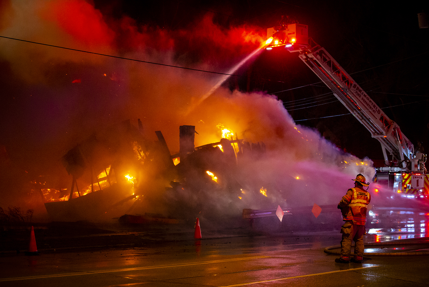 Truck One from the Springfield Fire Department contends with sustained winds over 20 mph as they attack a structure fire from the air with an aerial bucket as the fire fully engulfs a building at the corner of South Second Street and East Laurel Street, Sunday, March 10, 2019, in Springfield, Ill.