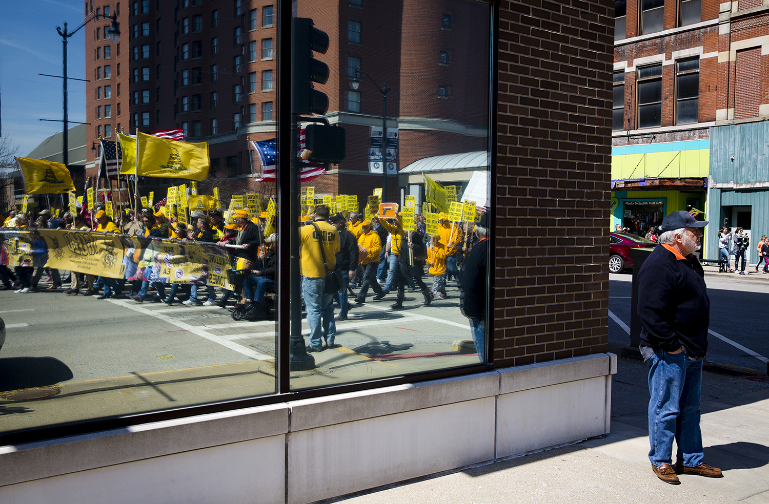 Gun rights advocates begin their march from the Bank of Springfield Center to the Capitol—the group reflected in the window of a building—during the Illinois State Rifle Association's annual gun owner's lobby day (IGOLD) Wednesday, March 27, 2019 in Springfield, Ill. [Rich Saal/The State Journal-Register]