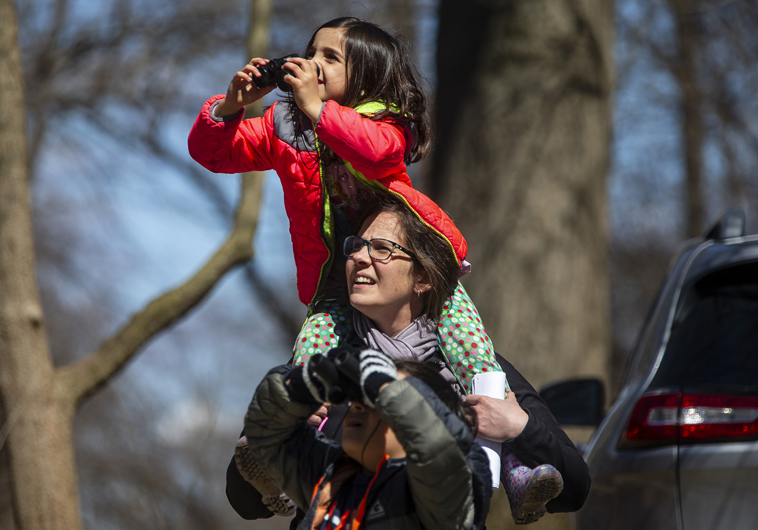 Norah Perry, 5, readies her binoculars from the shoulders of her mother, Denise Perry, center, as she and her brother Benjamin Perry, 9, try to catch a glimpse of a bird species pointed out during a guided bird watching walk hosted by Slow Food Springfield during the annual Pancake Breakfast at Lincoln Memorial Garden, Sunday, March 31, 2019, in Springfield, Ill. [Justin L. Fowler/The State Journal-Register]