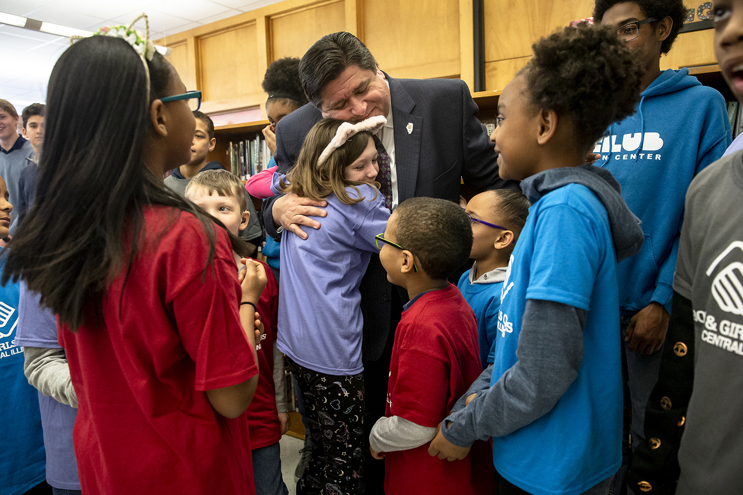 Illinois Governor J.B. Pritzker gets a hug from Abby Tavender, 10, while visiting with members of the Boys and Girls Clubs of Central Illinois after holding a press conference to sign HB 2505, a bill allowing universities to retain unused AIM HIGH scholarship funds and allow for flexibility administering the program, at Southeast High School, Thursday, April 4, 2019, in Springfield, Ill. [Justin L. Fowler/The State Journal-Register]