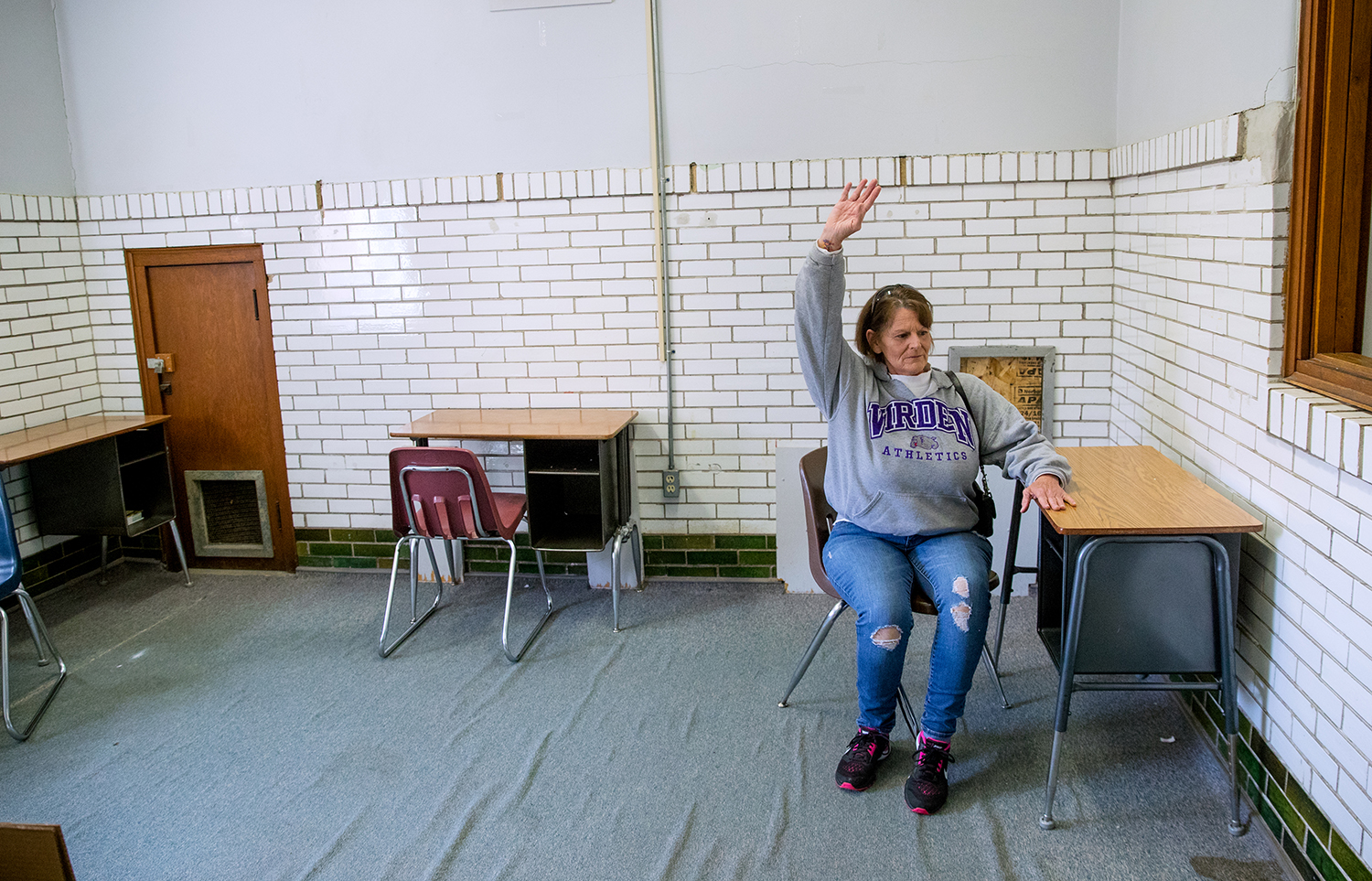 Sheila Crays raises her hand while sitting in a desk in an empty classroom at Virden Community High School during an open house Saturday, April 13, 2019. The old school buildings are being razed to make way for new North Mac High School facilities on the same property. Crays and her 11 siblings attended school in Virden. [Ted Schurter/The State Journal-Register]