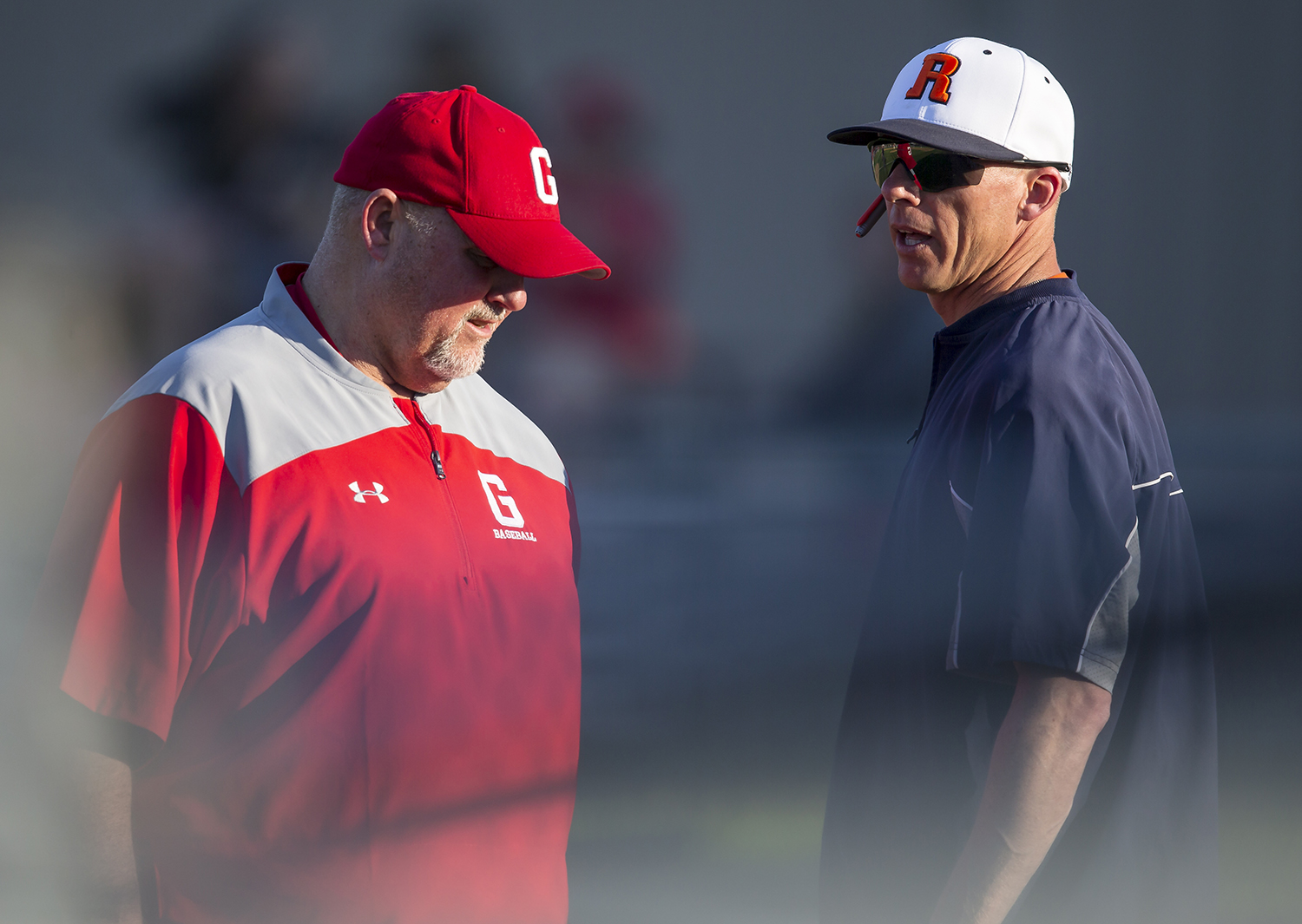 Rochester head coach Matt Carlson talks with Glenwood head coach Pat Moomey after the sixth inning at Rochester High School, Tuesday, April 16, 2019, in Rochester, Ill. [Justin L. Fowler/The State Journal-Register]