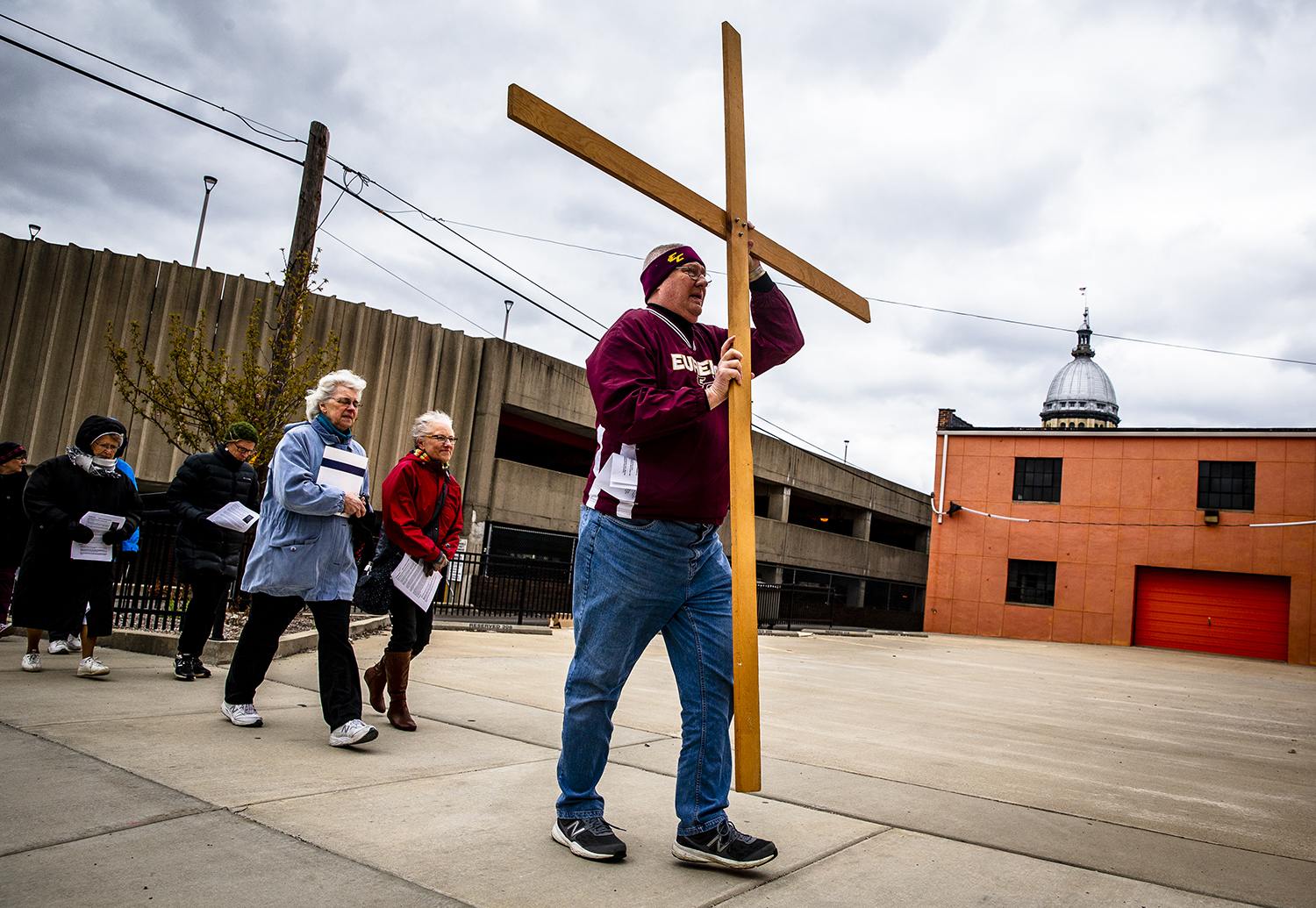 Bruce Bangert leads a group carrying a cross up South Fourth Street to the fourth of fourteen stops during the annual Good Friday Way of the Cross walk sponsored by the First Church of the Brethren, Hospital Sisters of St. Francis, Pax Christi Springfield and the Springfield Dominican Sisters, Friday, April 19, 2019, in Springfield, Ill. The Good Friday Way of the Cross connects social justice themes to locations, buildings and institutions around downtown Springfield. The fourth stop was a theme of violence and stoped in front of the Dept. of Children and Family Services and highlighted the need to protect children. [Justin L. Fowler/The State Journal-Register]