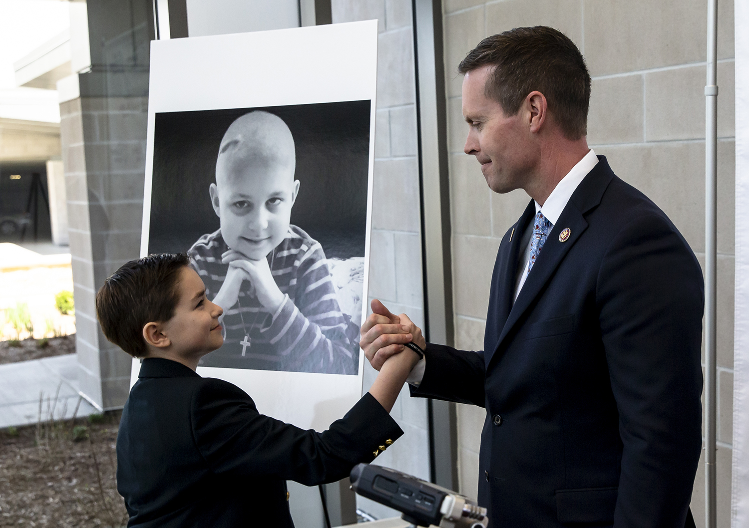 U.S. Rep. Rodney Davis, R-Taylorville, gets a hand shake from Jacky Wade, the twin brother of Jonny Wade pictured behind them who passed away from brain cancer on Christmas Eve in 2015, after the Wade family joined Davis to announce the Jonny Wade Pediatric Cancer Research Act (H.R. 2234) at HSHS St. John's Women and Children's Clinic, Monday, April 22, 2019, in Springfield, Ill. The bill, sponsored by Davis, would eliminate the Presidential Election Campaign Fun and transfer the #372.8 Million balance to a 10-year Pediatric Research Initiative Fund for pediatric cancer research. [Justin L. Fowler/The State Journal-Register]