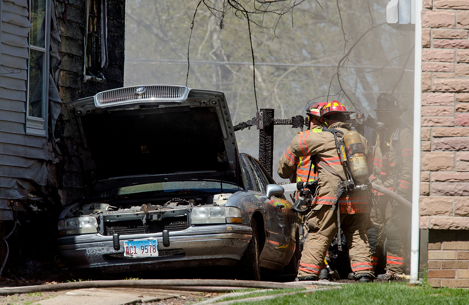 Springfield firefighters spray water into a car at 1023 Bryn Mawr Blvd. Sunday, April 21, 2019. The fire spread to the houses on both sides of the car. [Ted Schurter/The State Journal-Register]