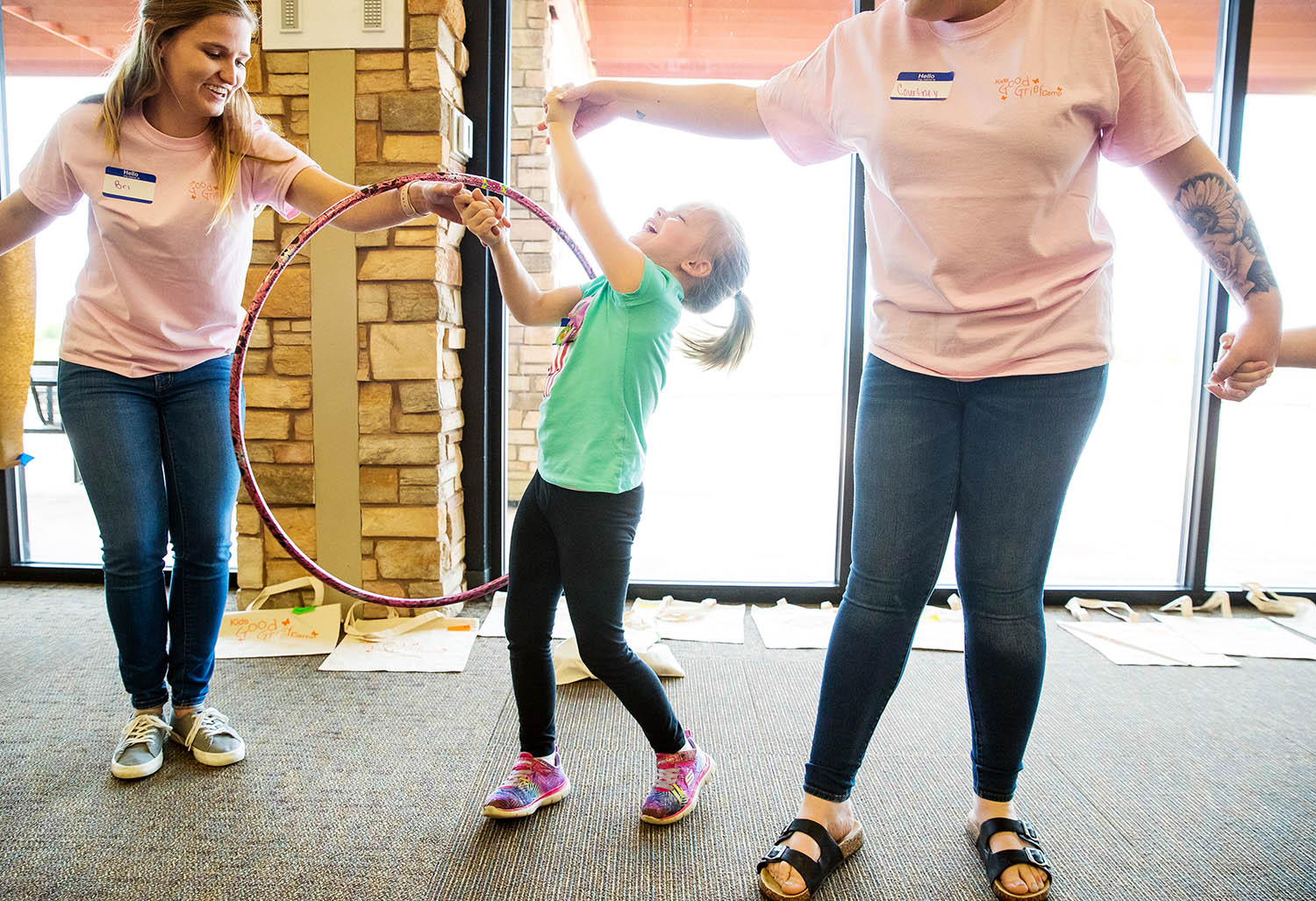 """Channing Walton, center laughs as she tries to maneuver a hoolahoop from Courtney Atwood, right to Bri Kattelman during Staab Funeral Home's annual """"Kids Good Grief Camp"""" at Erin's Pavilion at Southwind Park Sunday, April 28, 2019. The camp is designed to help young grievers cope with the death of a loved one. [Ted Schurter/The State Journal-Register]"""