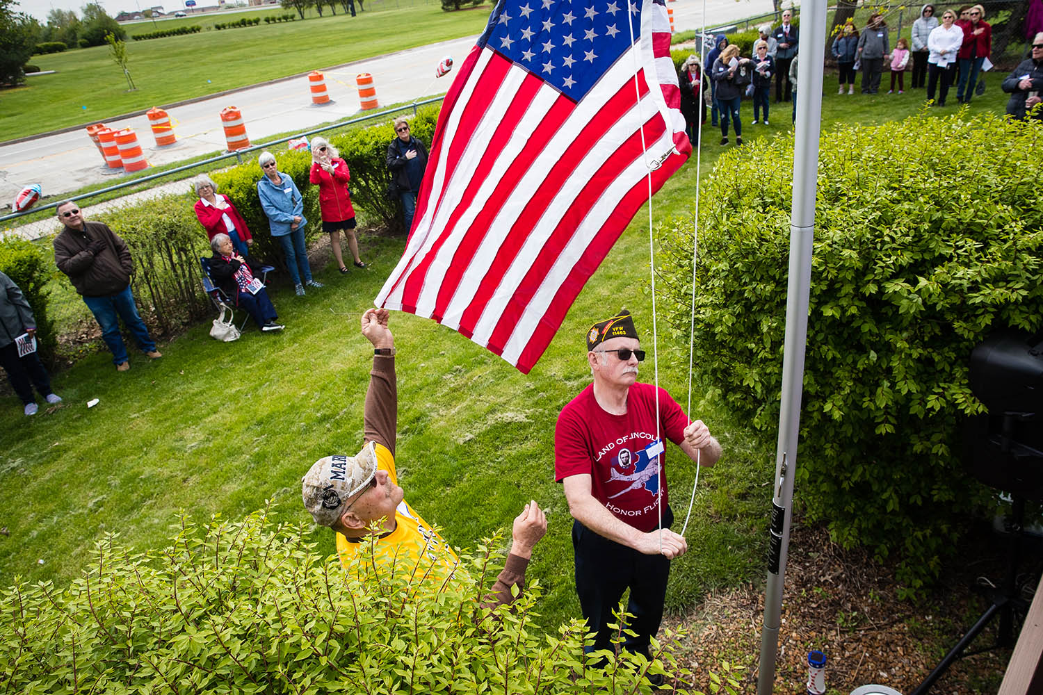 Veterans Weldon Stetter, left, and David Taft raise the U.S. flag on a new flag pole at Pat Kuster's Springfield home during a dedication ceremony Sunday, April 29, 2019. Kuster, a volunteer with Land of Lincoln Honor Flight, was the guardian for the two veterans on their trip to visit their memorials in Washington, D.C., and the host of the party that included prayers, a bugler and the singing of the national anthem and fundraising for the organization. [Ted Schurter/The State Journal-Register]