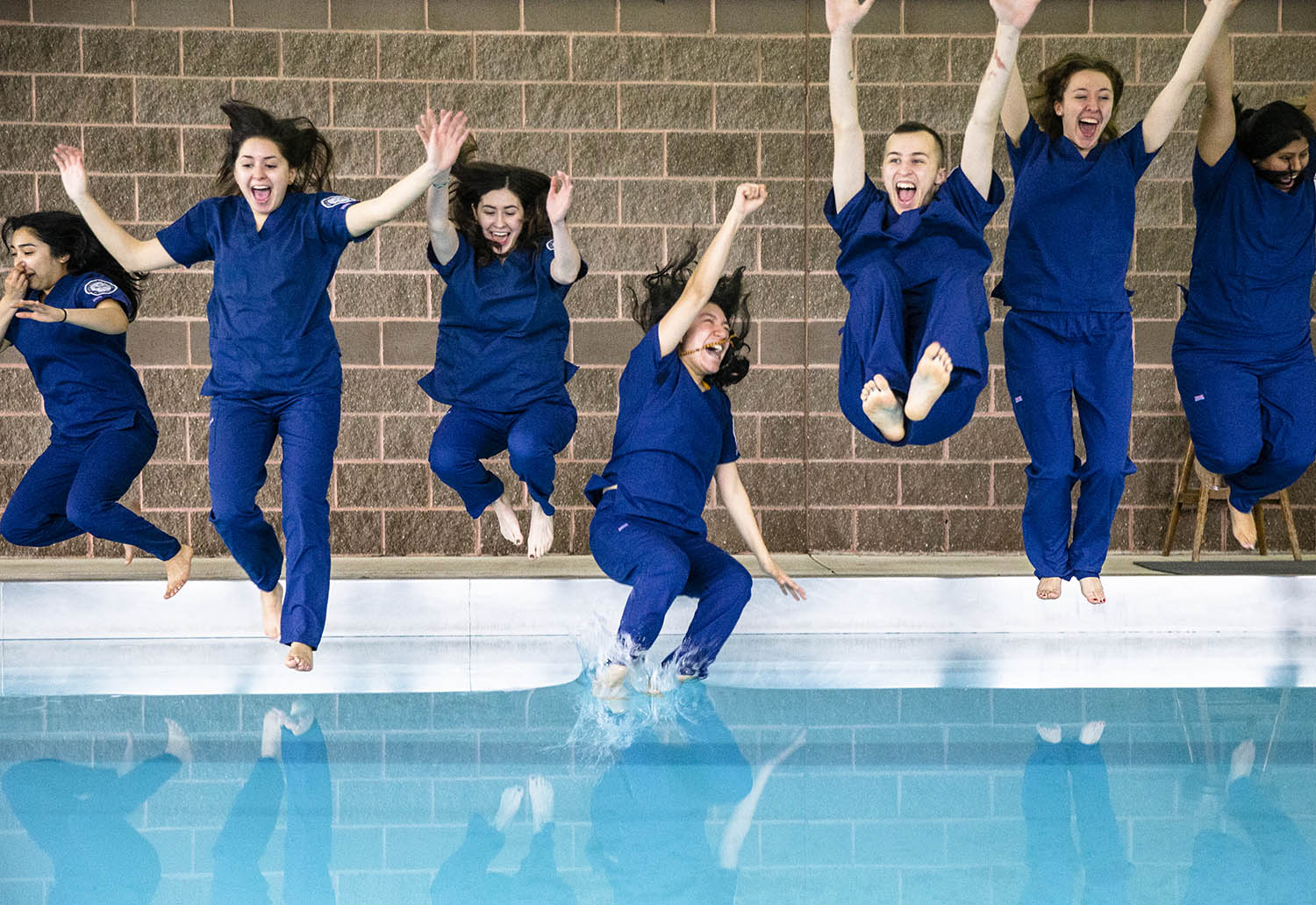 """Guadalupe Nino, center, of Chicago, Ill., hits the pool water first with the second graduating class of the University of Illinois at Chicago's College of Nursing Springfield Campus as the students perform the program's first """"Pool Jump"""" to celebrate graduating with their bachelor's degree in nursing, or BSN, at FitClub South, Friday, May 3, 2019, in Springfield, Ill. The tradition of the """"Pool Jump"""" goes back to over 30 years ago to the UIC main campus and is believed to be a twist on the Nightingale Pledge, a professional oath for nurses named in honor of Florence Nightingale. [Justin L. Fowler/The State Journal-Register]"""