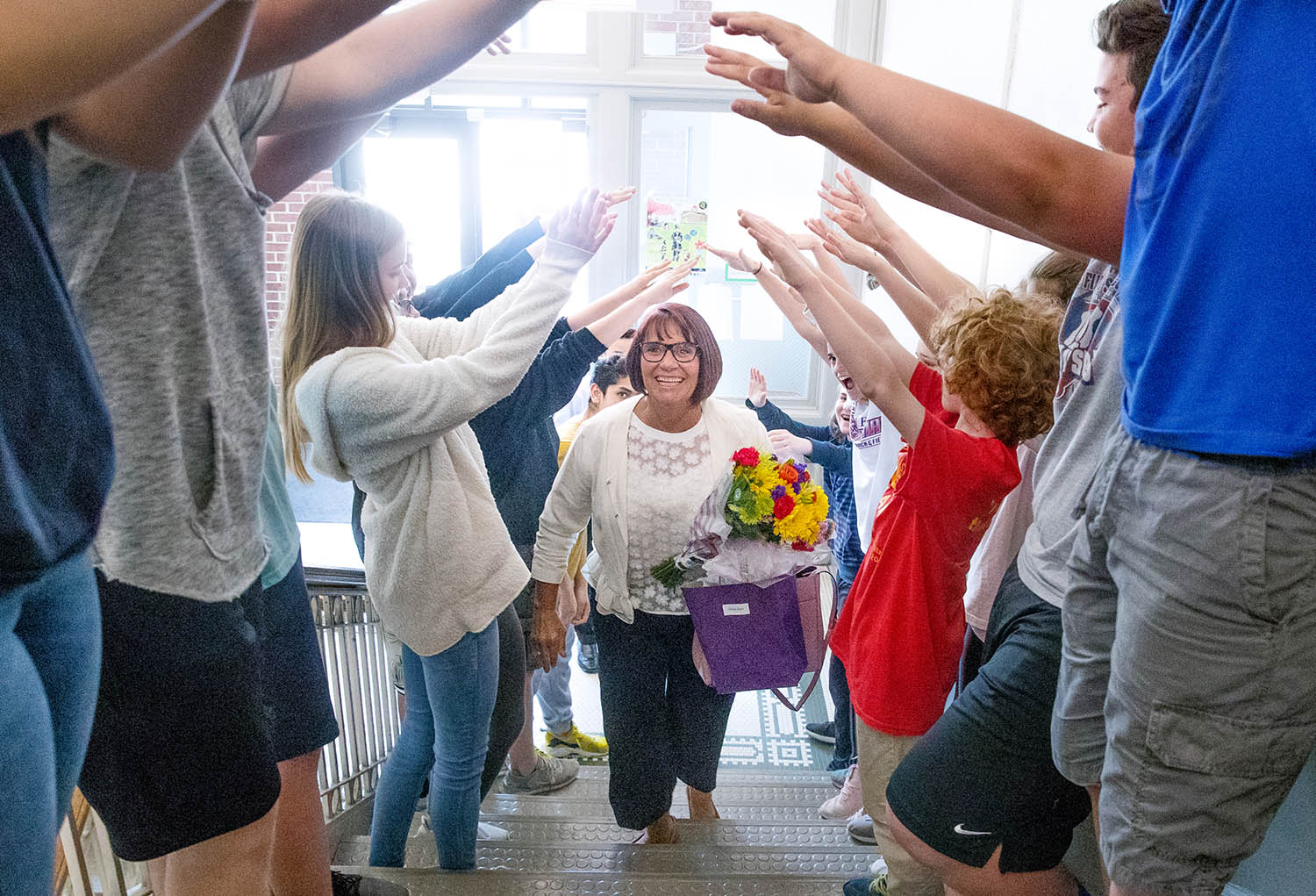 Christie Jones, an eighth grade writing, literature, and AVID teacher at Lincoln Magnet School, is greeted by students as she returns to the building after being named the 2019 Horace Mann Educator of the Year during a ceremony Tuesday, May 7, 2019. [Ted Schurter/The State Journal-Register]