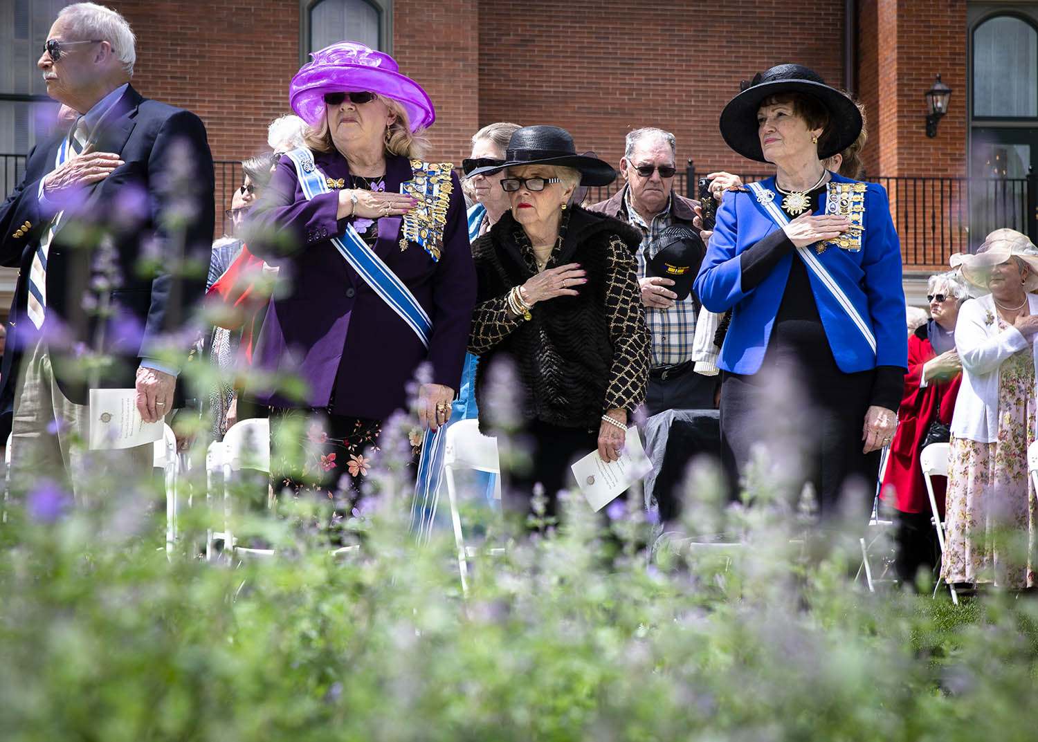 Luanne Bruckner, left, a past Vice President of the Illinois Daughters of the American Revolution, Gale Fixmer, center, a past vice president of the IDAR, and Pamela Bork, right, an honorary state regent for IDAR, hold their hands over their heart during the Presentation of Colors by the Chatham American Legion Post #759 during the dedication ceremony for the rose garden that was a gift from the IDAR and was funded for the Illinois Bicentennial at the Illinois Governor's Mansion, Friday, May 10, 2019, in Springfield, Ill. [Justin L. Fowler/The State Journal-Register]