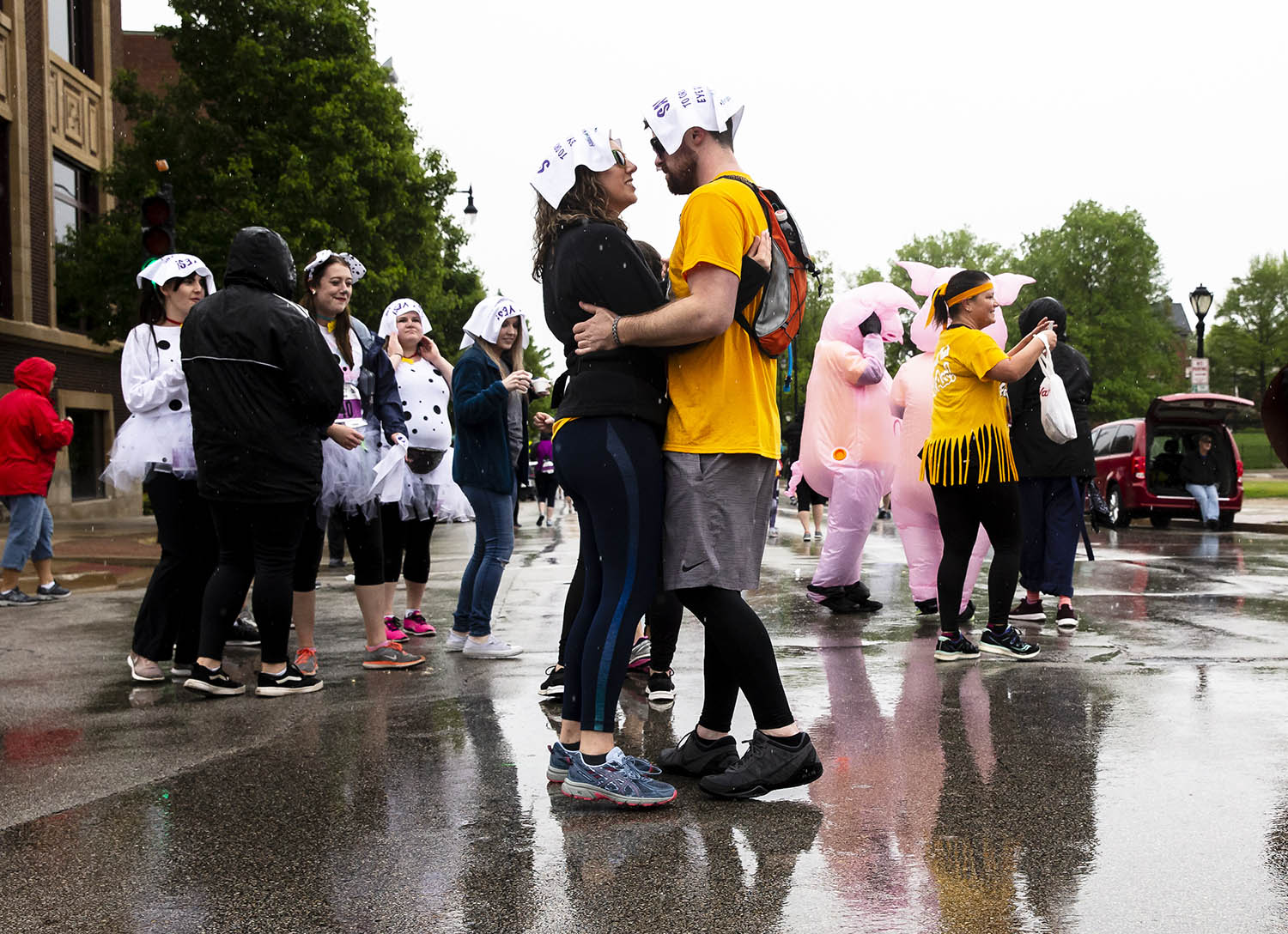 Rachel Stahl, left, and Christian Gillespie, right, dance in the rain to a performance of Elvis Himselvis along Capitol Avenue during the Fat Ass 5K & Street Party for Charity along the streets of downtown, Saturday, May 11, 2019, in Springfield, Ill. Stahl is originally from Springfield, but the couple traveled from Oklahoma to attend the race which was her sixth. The Fat Ass 5K is a race throughout downtown that includes stops for beer, corn dogs, donuts and ice cream and has donated over $1.3 million dollars to charity since 2008. According to Paul Schafer, one of the several race organizers, this year's event raised around $150,000 dollars that will be divided up between 36 charities. [Justin L. Fowler/The State