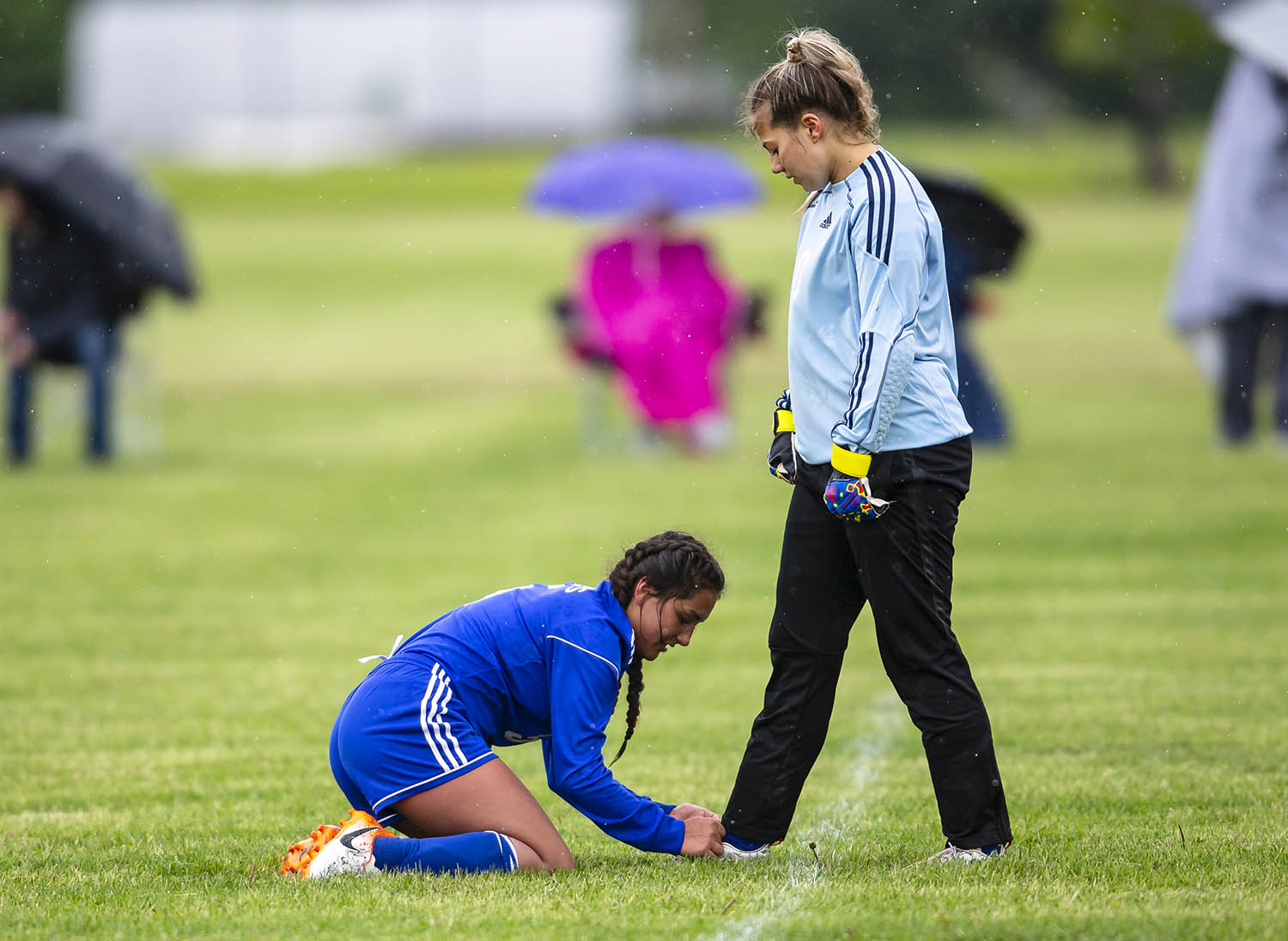 Lutheran's Bailey Wassell (5) helps Lutheran goal keeper Fran Adubato (1) tie her shoe as the Crusaders take on Williamsville in the second half during the Class 1A Riverton Regional Championship at the Riverton Field of Dreams, Saturday, May 11, 2019, in Riverton, Ill. [Justin L. Fowler/The State Journal-Register]
