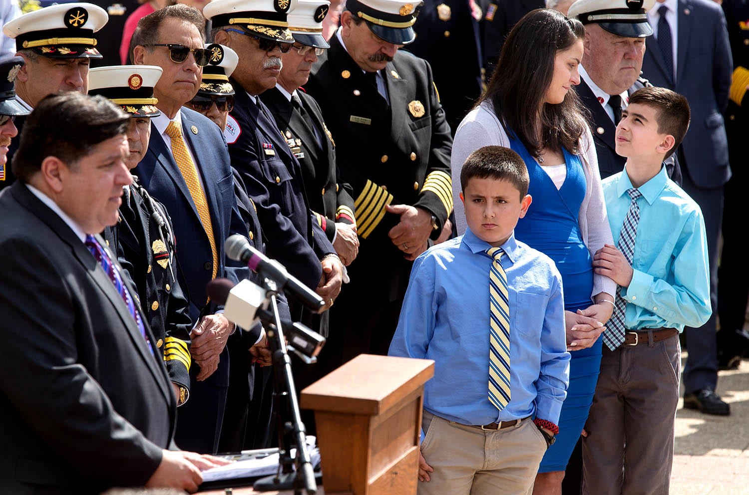 Joshua Bucio touches the arm of his mom, Amy Zabojnik, as Illinois Gov. J.B. Pritzker talks about his dad, Chicago firefighter Juan Bucio who was killed in the line of duty in May of 2018, during the 26th Annual Illinois Fallen Firefighter Memorial Ceremony at the Illinois Fallen Firefighter Monument Tuesday, May 14, 2019. Jacob is at right. [Ted Schurter/The State Journal-Register]