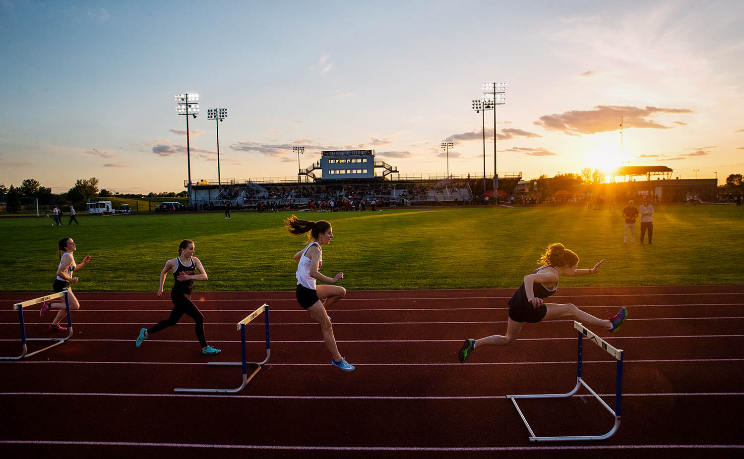 The field in the 300 meter hurdles makes their way down the back stretch as the sun sets during the Capital Area Classic Track Meet at Glenwood High School Monday, May 13, 2019. Athens' Morgan Penrod won the event. [Ted Schurter/The State Journal-Register]
