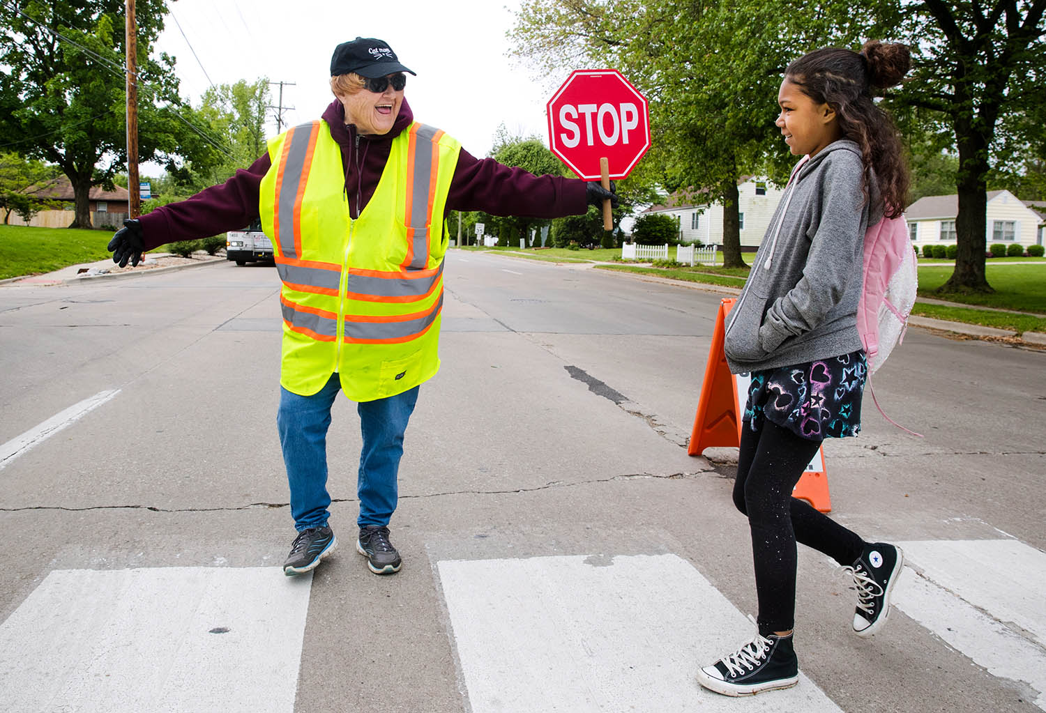 "Crossing guard Rita Kamnick greets fourth grader Janelle Shaw as she crosses Bruns Lane Tuesday, May 21, 2019. Illinois Gov. J.B. Pritzker declared May 21, as Crossing Guard Appreciation Day in Illinois to honor of the men and women who help ensure the safety of students throughout Illinois as they walk and bike to school. Kamnick sports a ""Cat Mom"" hat as a reference to all the ""kiddies"" she knows by name and cares for during the school year. [Ted Schurter/The State Journal-Register]"