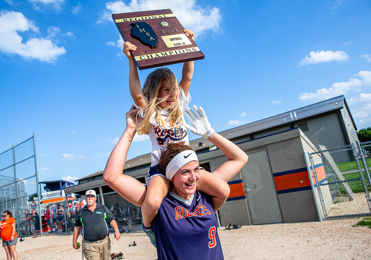 Blakely Howard, 5, celebrates with the championship plaque from the shoulders of Rochester's Reagan Miles (9) after the Rockets defeated Clinton 4-0 in the Class 3A Rochester Regional championship game at Rochester High School, Friday, May 24, 2019, in Rochester, Ill. [Justin L. Fowler/The State Journal-Register]