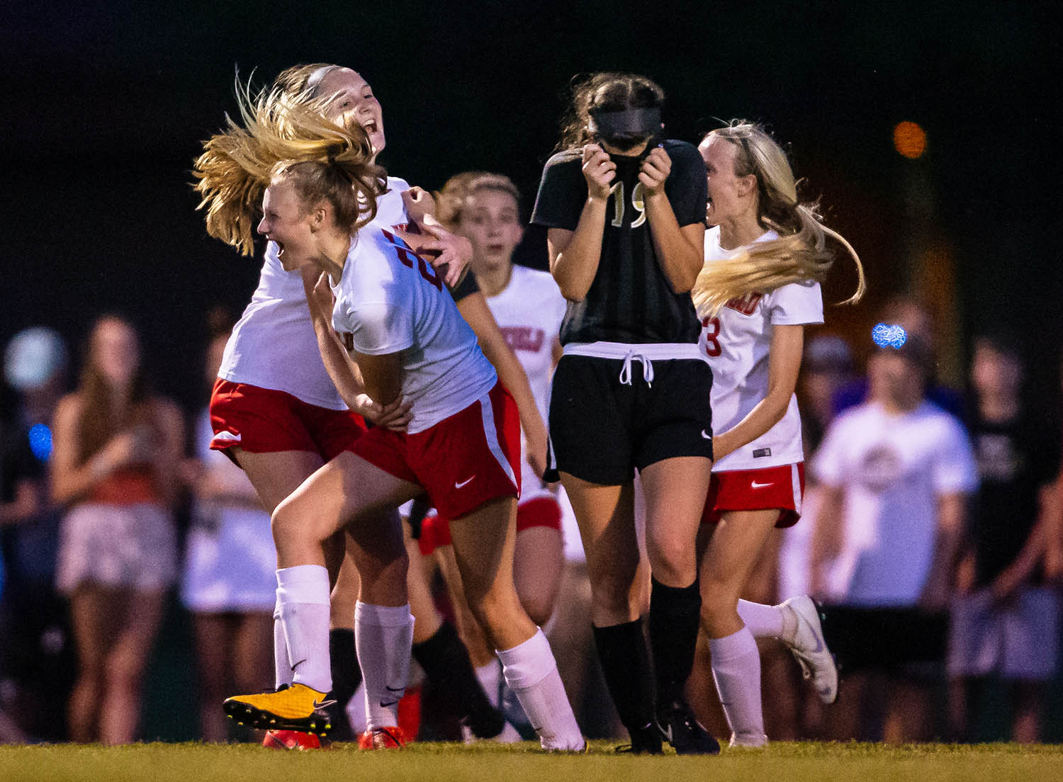 Springfield's Sarah Becker (25) celebrates with Springfield's Anna Lamsargis (12) while Sacred Heart-Griffin's Sophie Ludolph (19) walks off the field after the Senators defeated the Cyclones 2-1 in overtime in the Class 2A Rochester Sectional championship game at Rochester Elementary School, Friday, May 24, 2019, in Rochester, Ill. [Justin L. Fowler/The State Journal-Register]