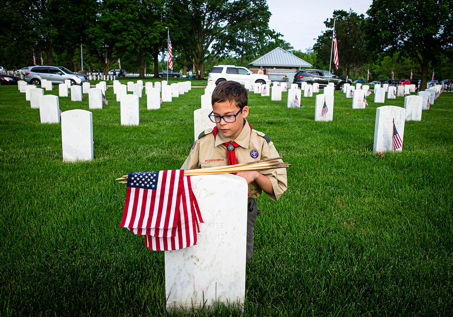 Ethan Perry, of New Berlin, Ill., with Boy Scout Troop 13, pauses at a gravestone to place an American Flag in honor of veterans for Memorial Day at Camp Butler National Cemetery, Saturday, May 25, 2019, near Riverton, Ill. The Boy Scouts join with veterans and volunteers in the annual tradition of placing an American Flag at every gravestone in the cemetery. [Justin L. Fowler/The State Journal-Register]