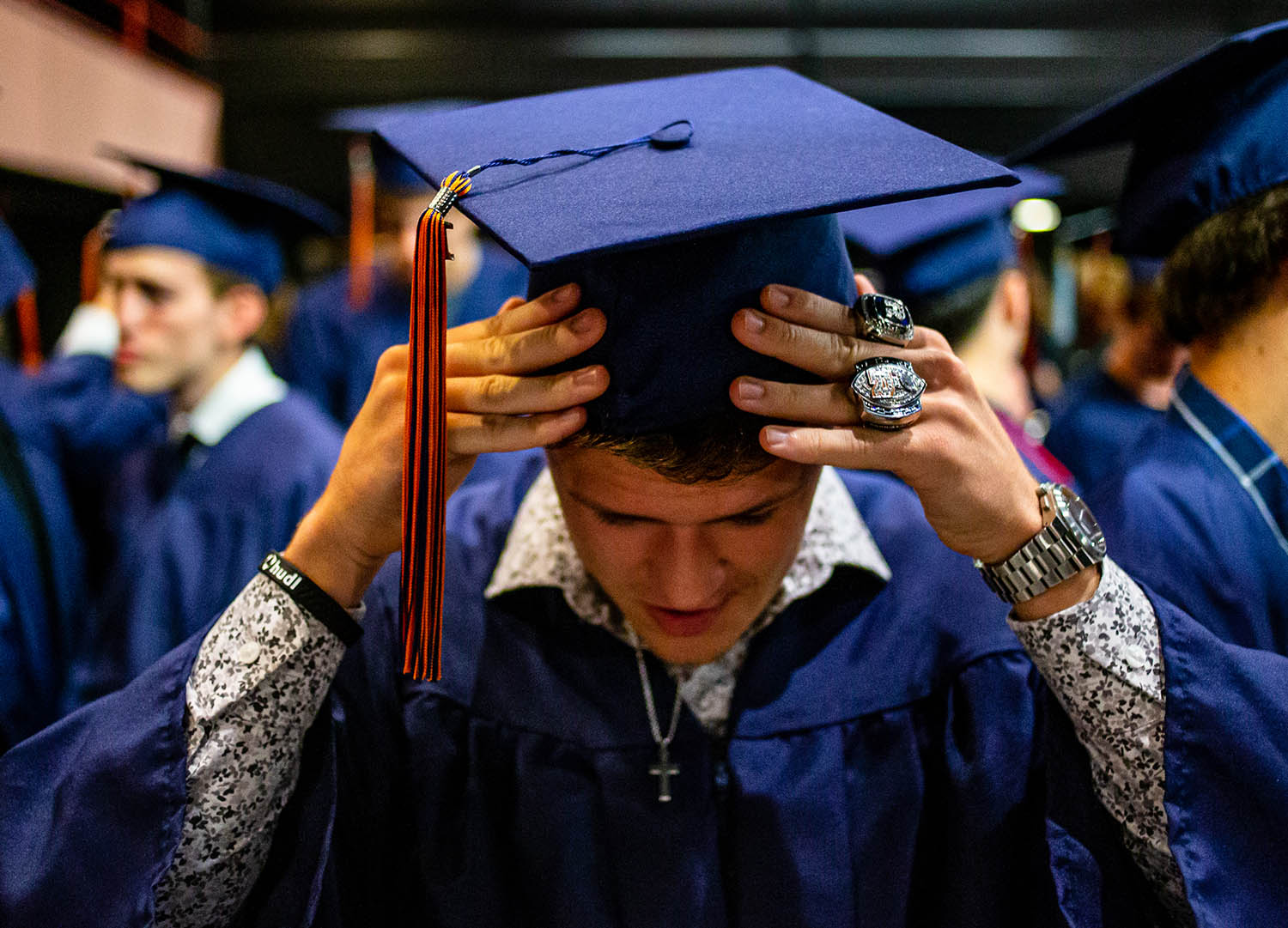 Cade Eddington adjusts his graduation cap while wearing the championship rings from his time playing football for Rochester High School as the Class of 2019 prepares for their graduation ceremony at the Sangamon Auditorium at the University of Illinois Springfield, Sunday, May 26, 2019, in Springfield, Ill. [Justin L. Fowler/The State Journal-Register]