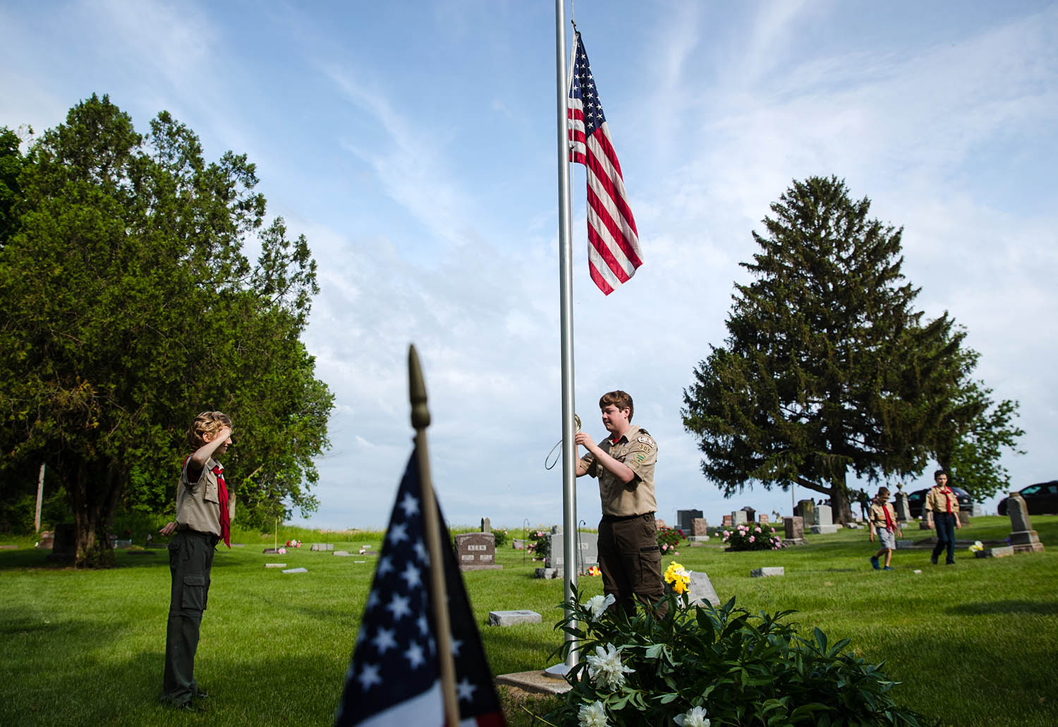 Boy Scout Troop 305 member Hugh Beeler salutes as Matt Shaw lowers the flag before a Memorial Day ceremony at Salisbury Cemetery Monday, May 27, 2019. The joint effort with American Legion Post 599 included stops at multiple cemeteries for a 21-gun salute and the playing of Taps. [Ted Schurter/The State Journal-Register]