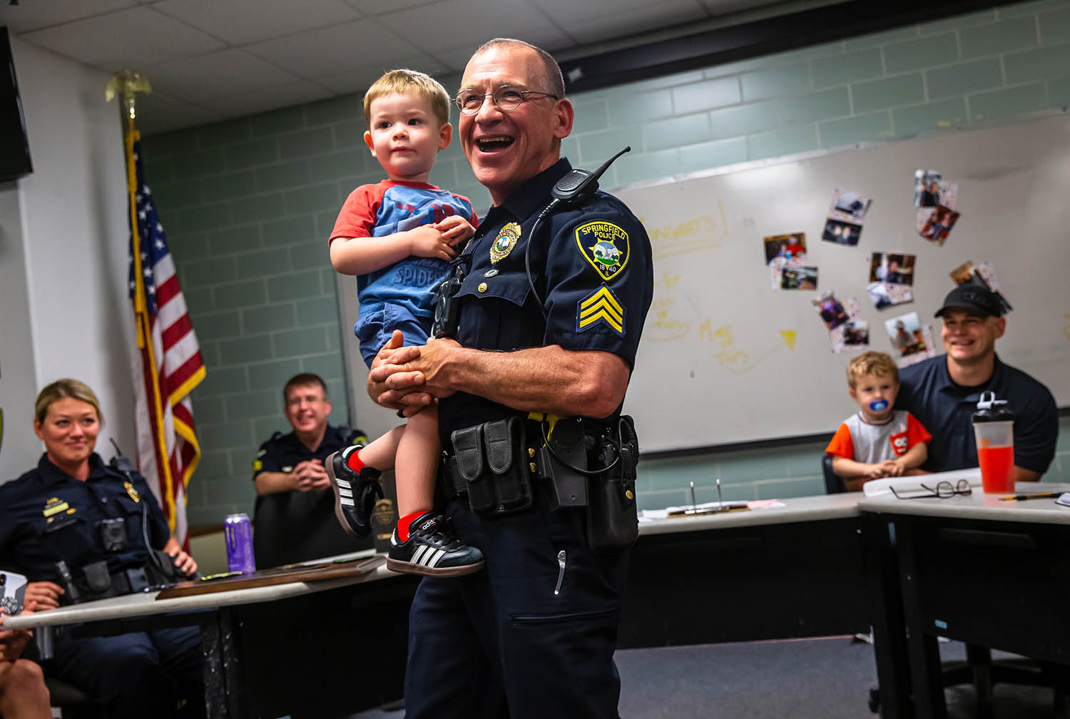 """Sgt. Gerry Castles thanks his family, friends and fellow police officers with the Springfield Police Department as he holds his grandson, Leo Warren, 2, during a ceremony marking his retirement after 28 years as a police officer during his last squad meeting at Municipal Center East, Friday, May 31, 2019, in Springfield, Ill. """"You get into this job because you think youÕre gonna effect peoples lives and then somewhere in it you finally realize that you really arenÕt...but within it there are specific lives you do affect,"""" said Castles as he reflected on cases where people have reached out to him after calls to tell him that he saved their lives. [Justin L. Fowler/The State Journal-Register]"""