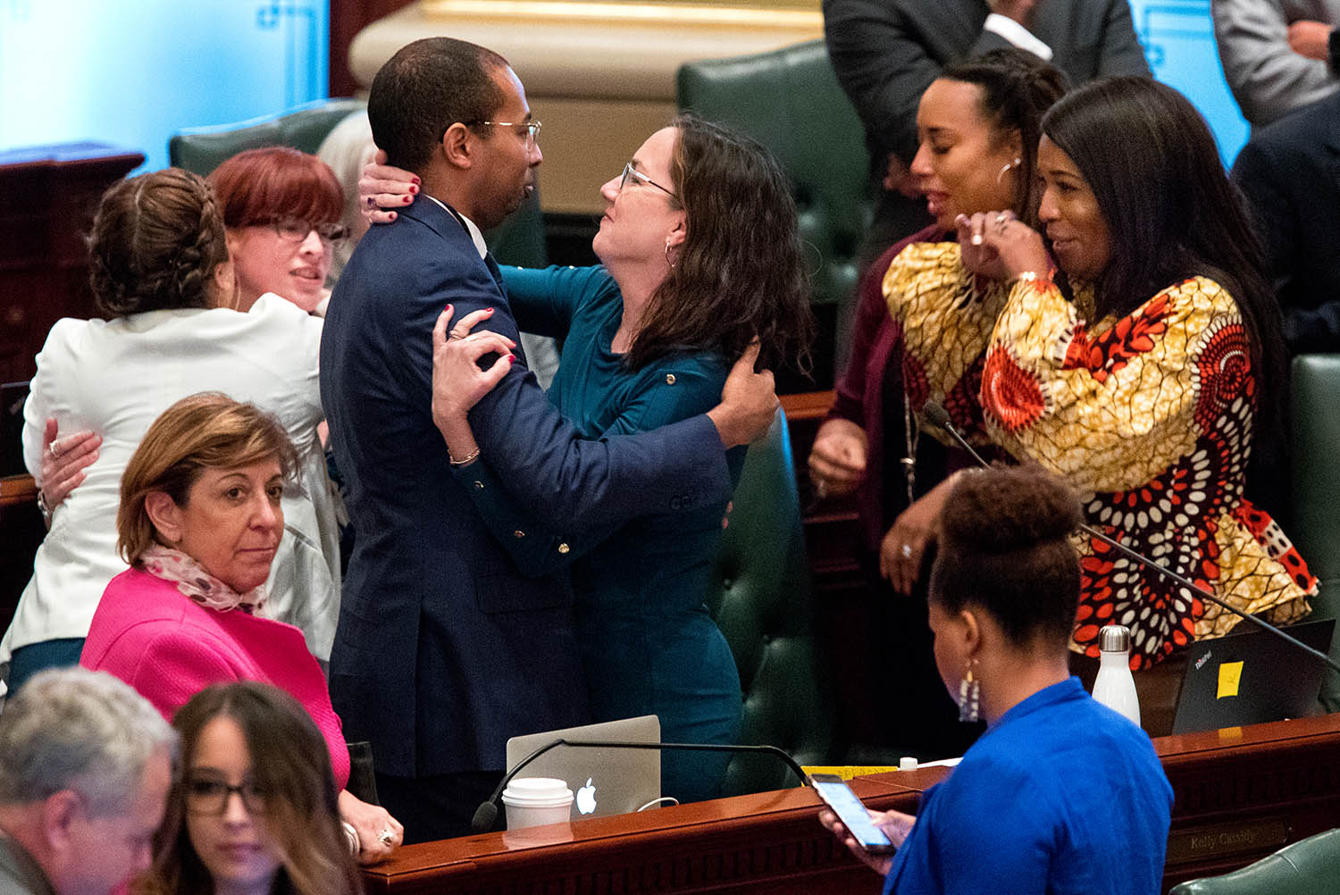 Illinois deputy governor Christian Mitchell and Illinois state Rep. Kelly Cassidy, D-Chicago, embrace as they celebrate the 66-47 vote in the Illinois House for a bill to legalize recreational marijuana use Friday, May 31, 2019. The vote sends the bill to Gov. J.B. Pritzker who indicated he will sign it. [Ted Schurter/The State Journal-Register]