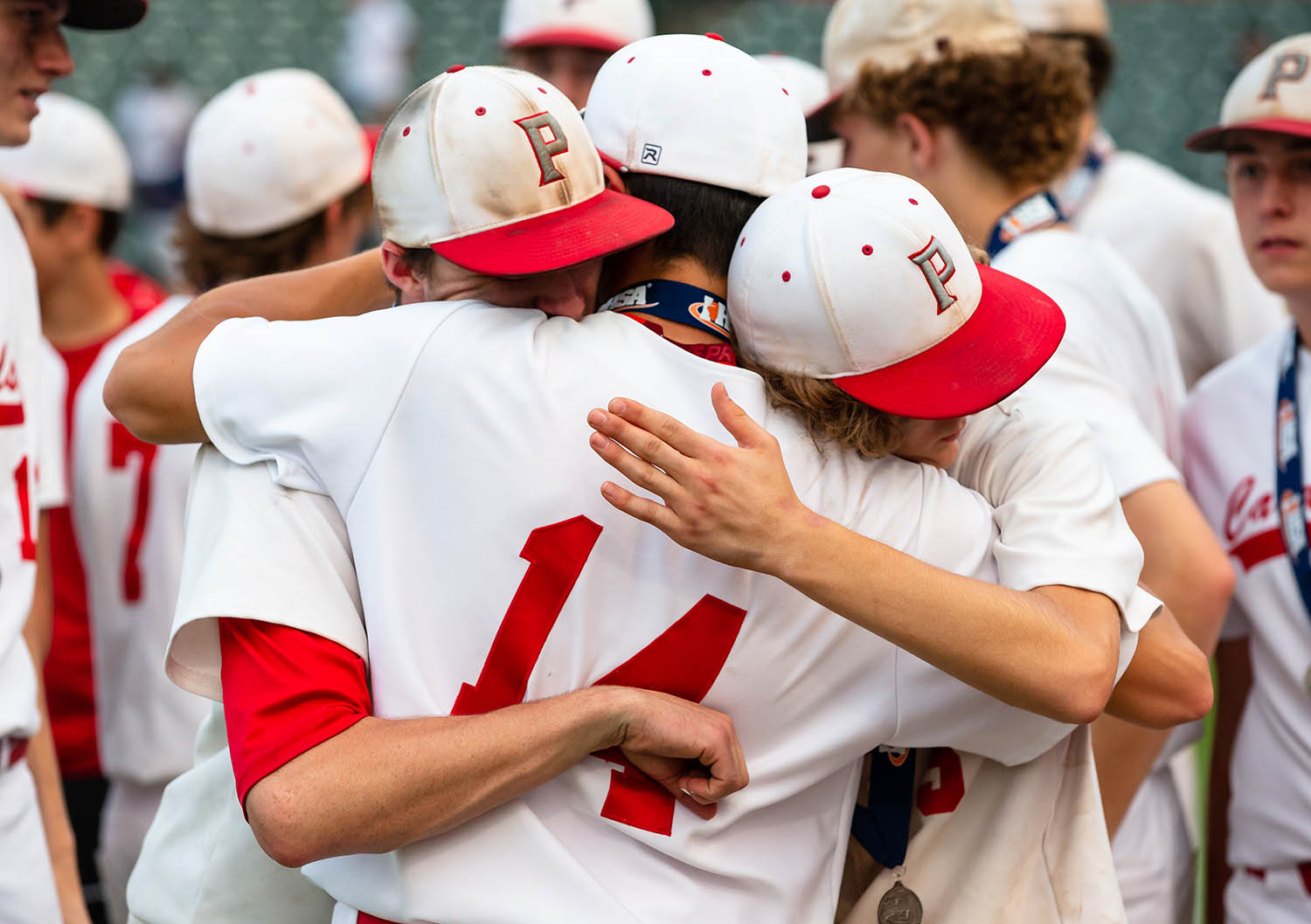 Pleasant Plains' Corgan Greer (13) hugs Joe Lee (14) and Reese Snell (3) after the Cardinals were defeated by Teutopolis 12-6 in the IHSA Class 2A State Championship game at Dozer Park, Saturday, June 1, 2019, in Peoria, Ill. [Justin L. Fowler/The State Journal-Register]