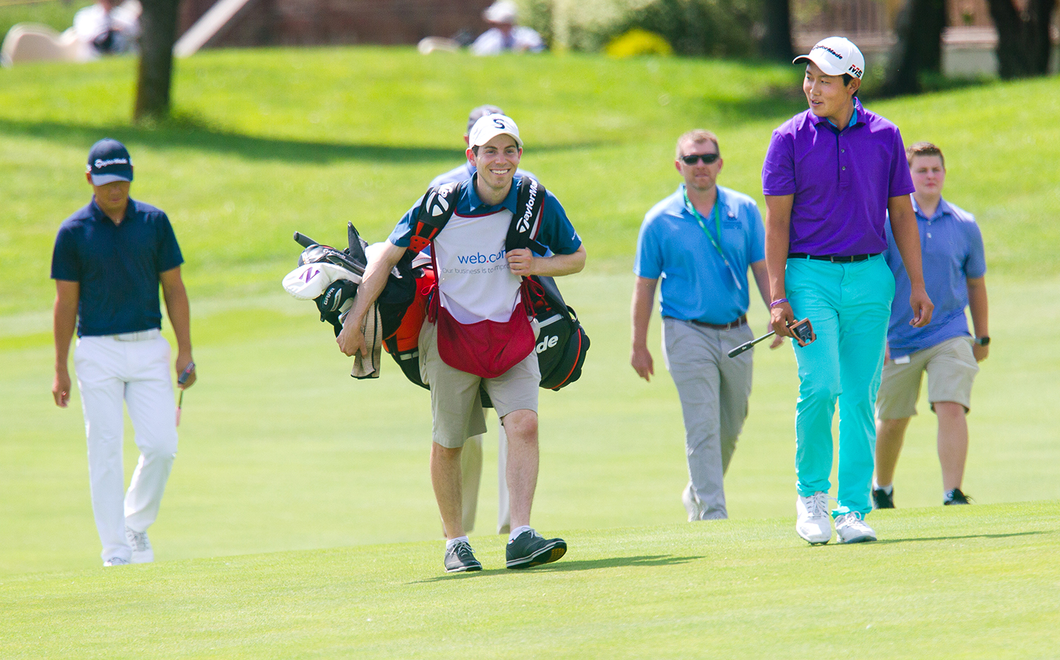 Dylan Wu jokes with his caddie and former Northwestern University teammate Harley Abrams as they approach the 18th green for the first playoff with Xinjun Zhang, left, during the fourth round of Web.com Tour's Lincoln Land Championship presented by LRS Sunday, June 16, 2019. Wu and Zhang tied the first two playoff holes before Zhang won on the third. [Ted Schurter/The State Journal-Register]