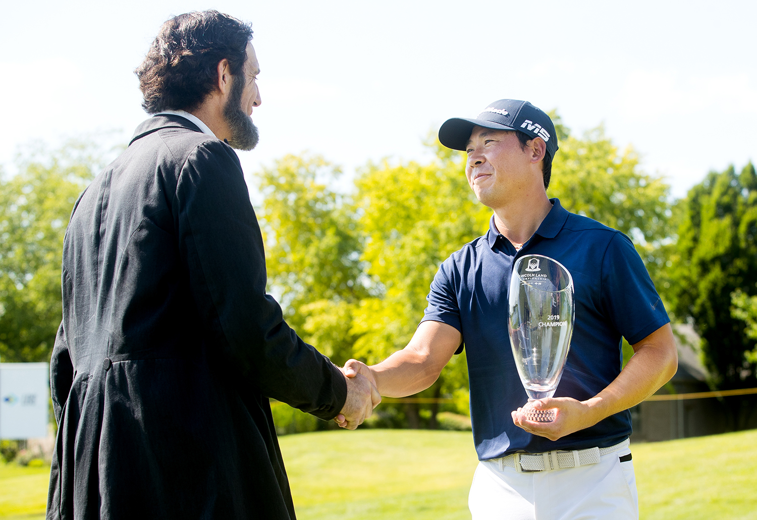 Randy Duncan, an Abraham Lincoln presenter, shakes hands with the 2019 Web.com Tour's Land of Lincoln Championship winner Xinjun Zhang on the 18th green at Panther Creek Country Club golf course Sunday, June 16, 2019. Zhang survived a three-hole playoff against Dylan Wu to earn his second tour win this year. [Ted Schurter/The State Journal-Register]