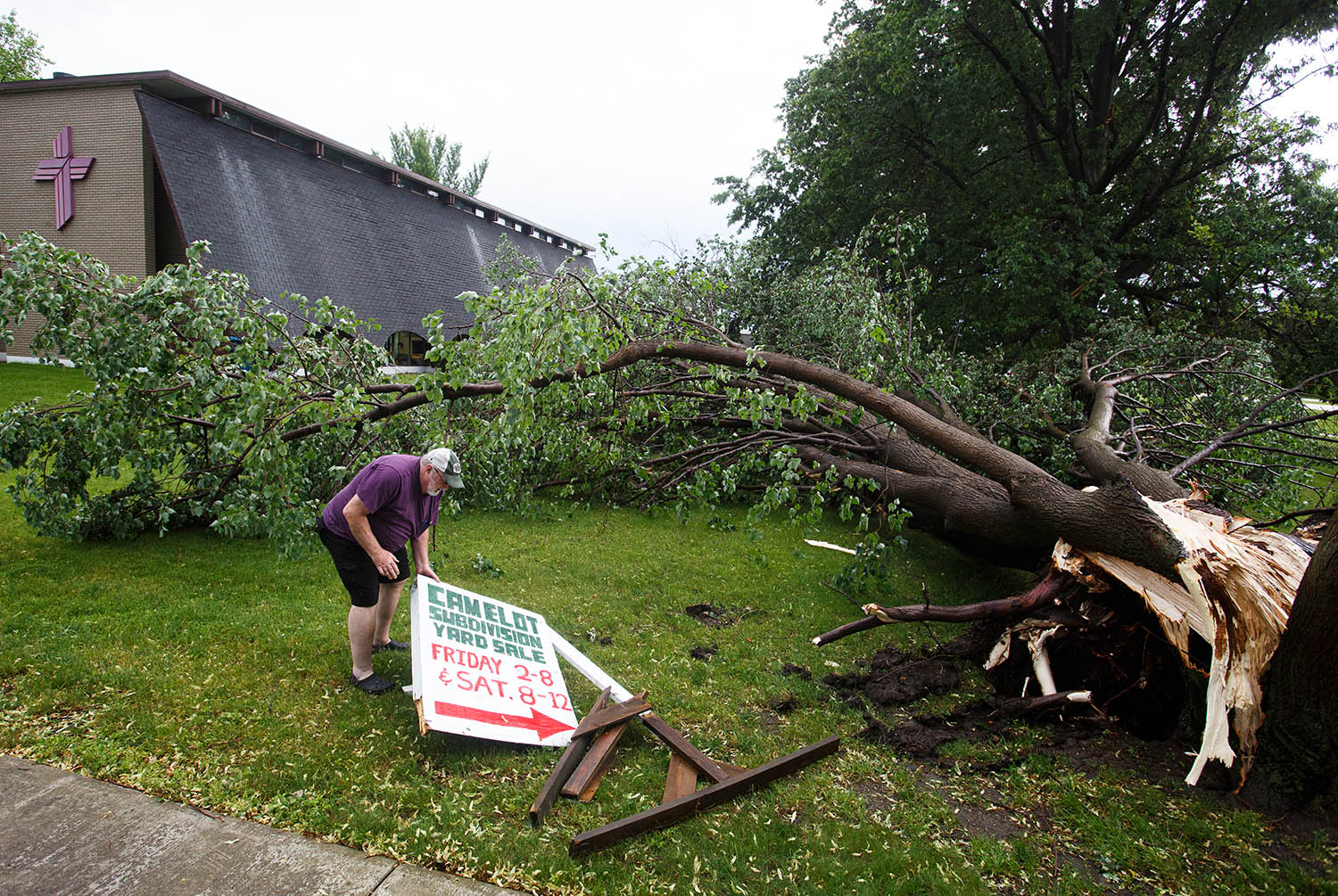 "Gary South, of Rochester, Ill., gathers the pieces of a sign advertising the Camelot Subdivision Yard Sale that the Good Shepard Lutheran Church participates in next to a linden tree that was blown over on the south side of the church after a strong storms moved through the area, Wednesday, June 5, 2019, in Rochester, Ill. ""It was very windy, it blew pretty hard,"" said South who was inside the church at the time of the storm. [Justin L. Fowler/The State Journal-Register]"