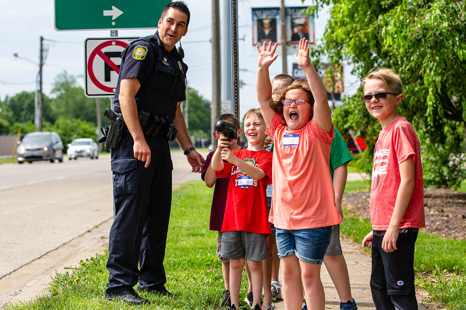"Margo Goldstein screams out for cars to ""slow down"" as Chatham Police Officer David Leach teaches children in the the department's Junior Cadet Academy about speed limits while letting them use a radar gun along South Main Street  next to the Chatham Square, Thursday, June 6, 2019, in Chatham, Ill. [Justin L. Fowler/The State Journal-Register]"