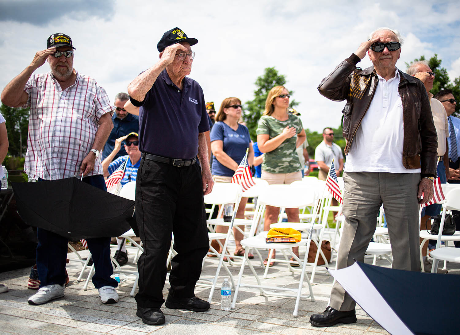 "Word War II Army veteran, Charles ""Ike"" Weishaar, stands to salute along with his son, Steve Weishaar, left, a Vietnam veteran, and fellow WWII veteran Rev. Gerald ÒJerryÓ Raschke, right, during a ceremony marking the 75th Anniversary of D-Day at the World War II Illinois Veterans Memorial at Oark Ridge Cemetery, Thursday, June 6, 2019, in Springfield, Ill. Weishaar served in the Army in the European Theatre on a 90mm anti-aircraft gun. [Justin L. Fowler/The State Journal-Register]"