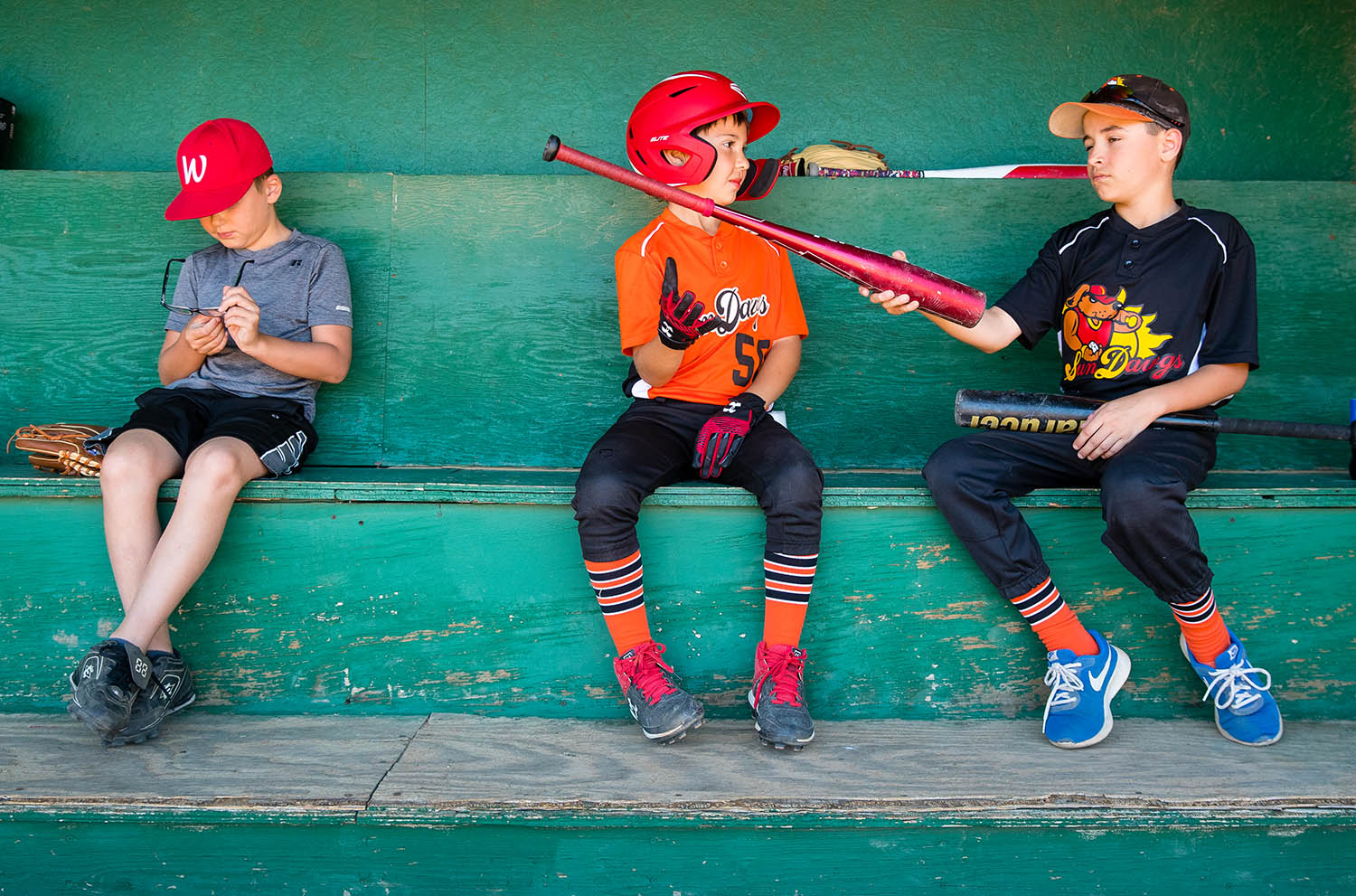 Caiden Bietsch assess the weight of Adam McCloughan bat as they talk about equipment while they wait their turn at the plate during Lincoln Land Community College Fundamental Skills Camp Monday, June 10, 2019. The camp offers personal and group instruction on all aspects of the game. Vinny Viele is at left. [Ted Schurter/The State Journal-Register]