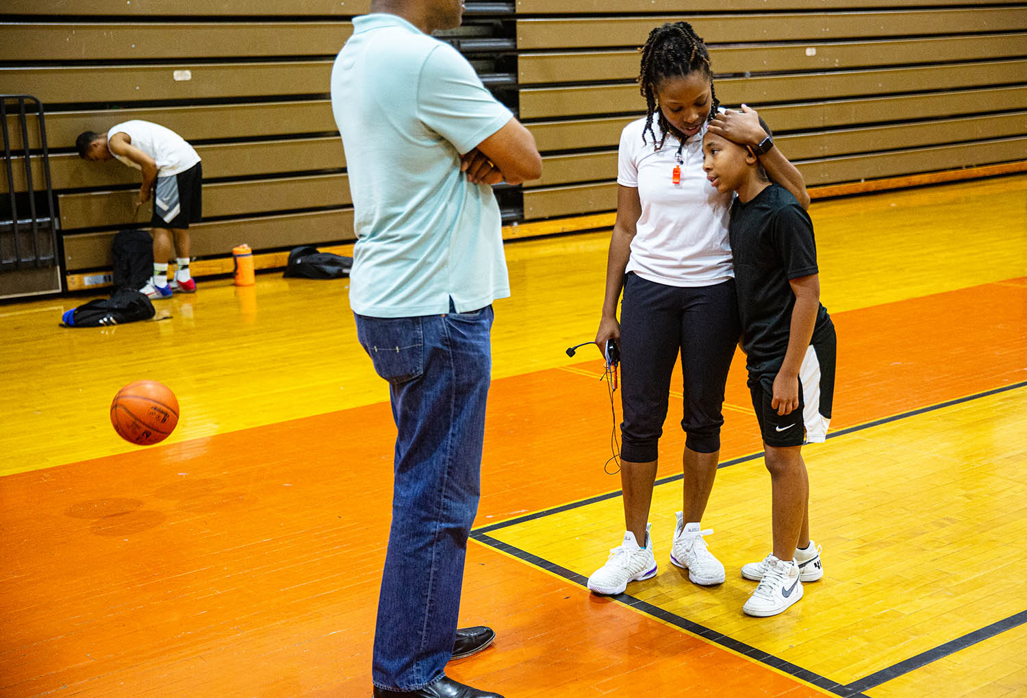 "Marke Freeman, center, a former Lanphier High School and professional basketball player, gives Jayden Jefferson, 10, at the end of a day of camp during the 8th Annual Marke Freeman Max-OUT Basketball Camp at Lanphier High School, Wednesday, June 12, 2019, in Springfield, Ill. Freeman created the Max-OUT camp in 2011 that uses basketball as a base to ""Maximizing Opportunities, Unity, and Training in our communing,"" to over 130 youths attending the camp. [Justin L. Fowler/The State Journal-Register]"