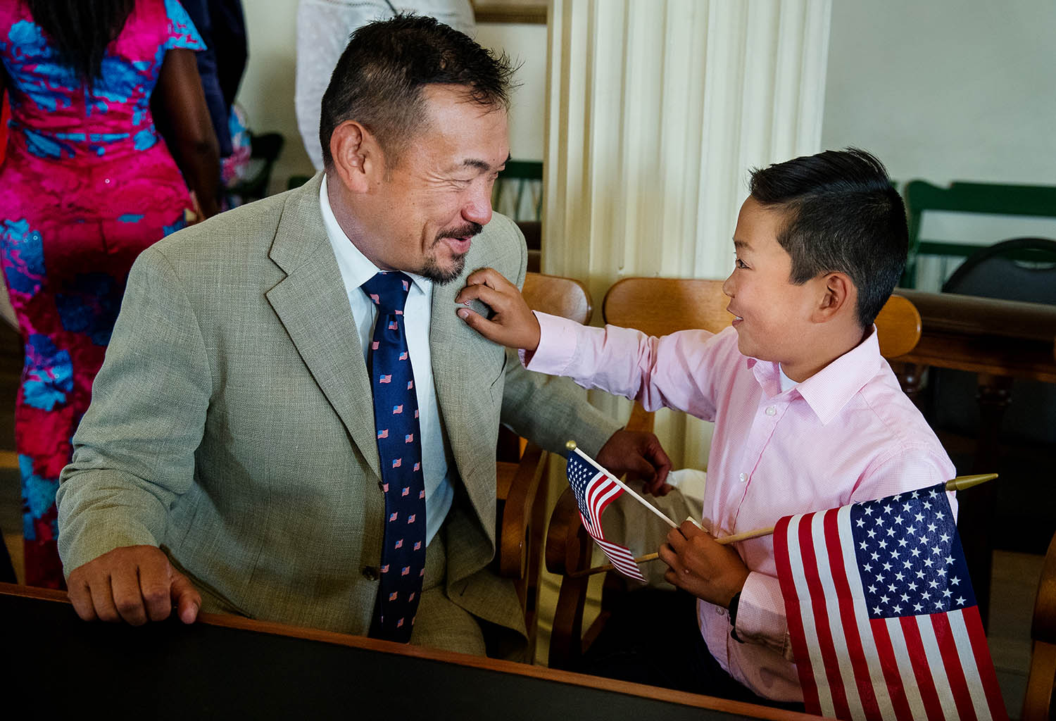 Toshi Maeda laughs as his son James investigates his U.S. flag lapel pin after a naturalization ceremony at the Old State Capitol Friday, June 14, 2019. Sixty-three new citizens were sworn-in during the ceremony. [Ted Schurter/The State Journal-Register]