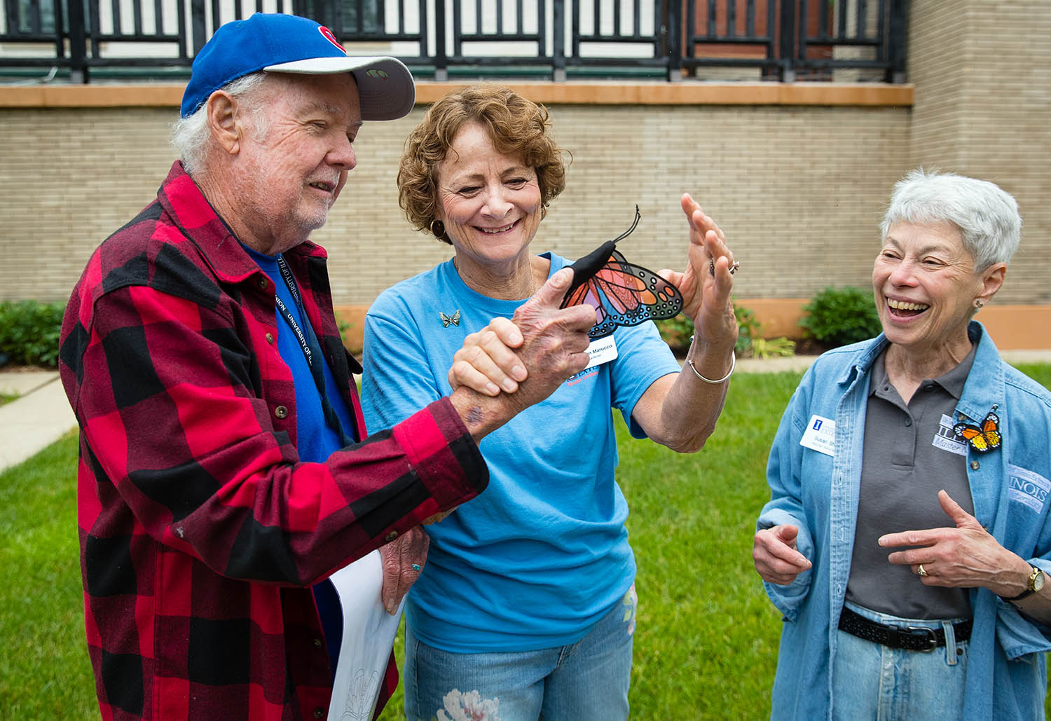 "Bill Kinzer laughs as Sharon Marucco helps him fit a butterfly prop on his finger in the courtyard of the Dana-Thomas House State Historic Site as they await guests for the ""Butterflies and Bugs"" program presetned by University of Illinois Master Gardeners and Master Naturalist Saturday, June 15, 2019. The program highlighted Frank Lloyd's incorporation of butterfly motifs in different aspects of the house's design and included information on planting Pollinator Pocket gardens and planters to help attract butterflies and pollinators. Susan Shaw is at right. [Ted Schurter/The State Journal-Register]"