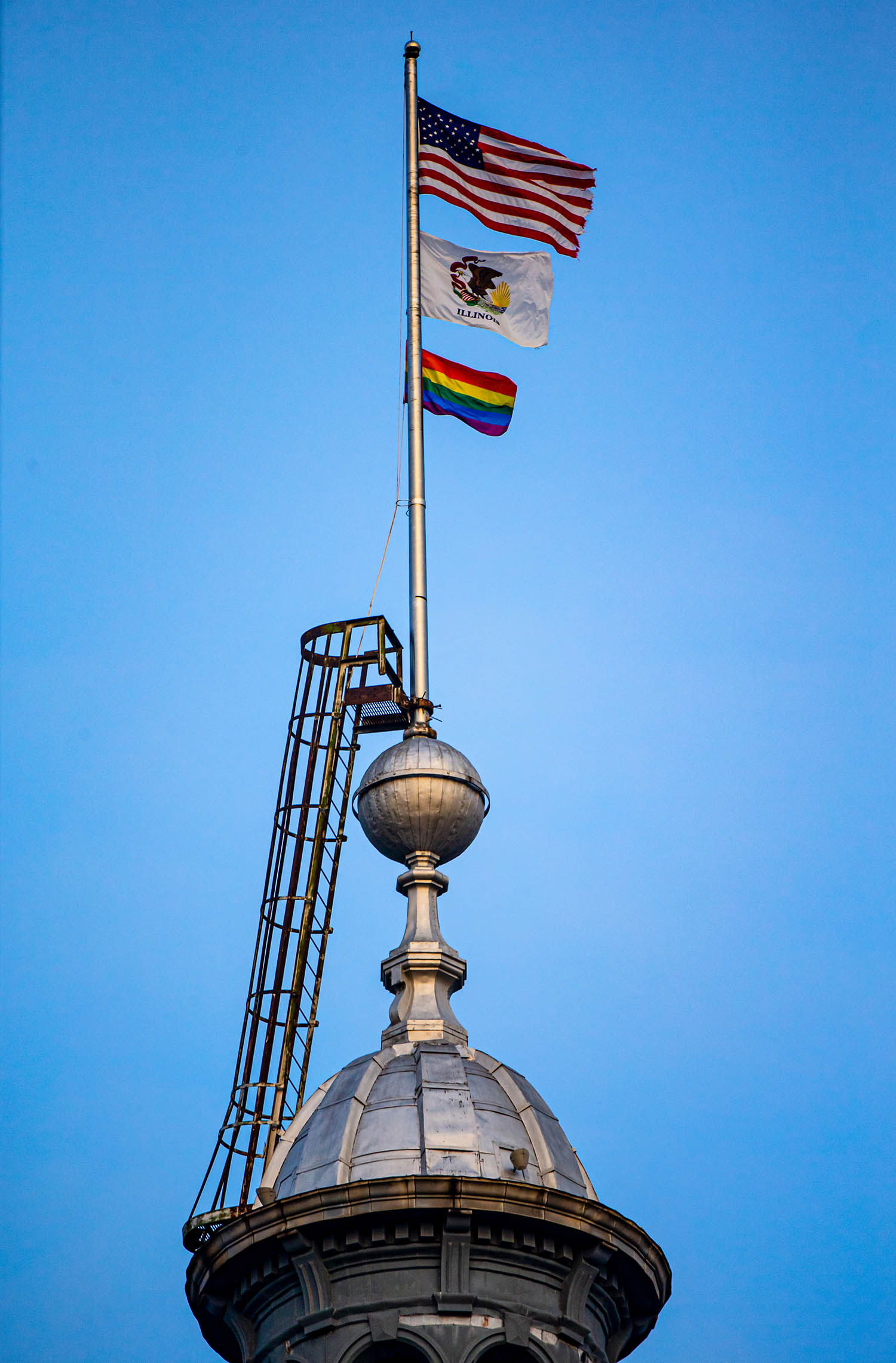 A rainbow pride flag flies along with the Illinois Flag and the American Flag atop the Illinois State Capitol to celebrate Pride Month at the request of Illinois Governor J.B. Pritzker, Monday, June 17, 2019, in Springfield, Ill. The rainbow pride flags were donated by Springfield´s Phoenix Center, the LGBTQ Community Center for Central Illinois. [Justin L. Fowler/The State Journal-Register]