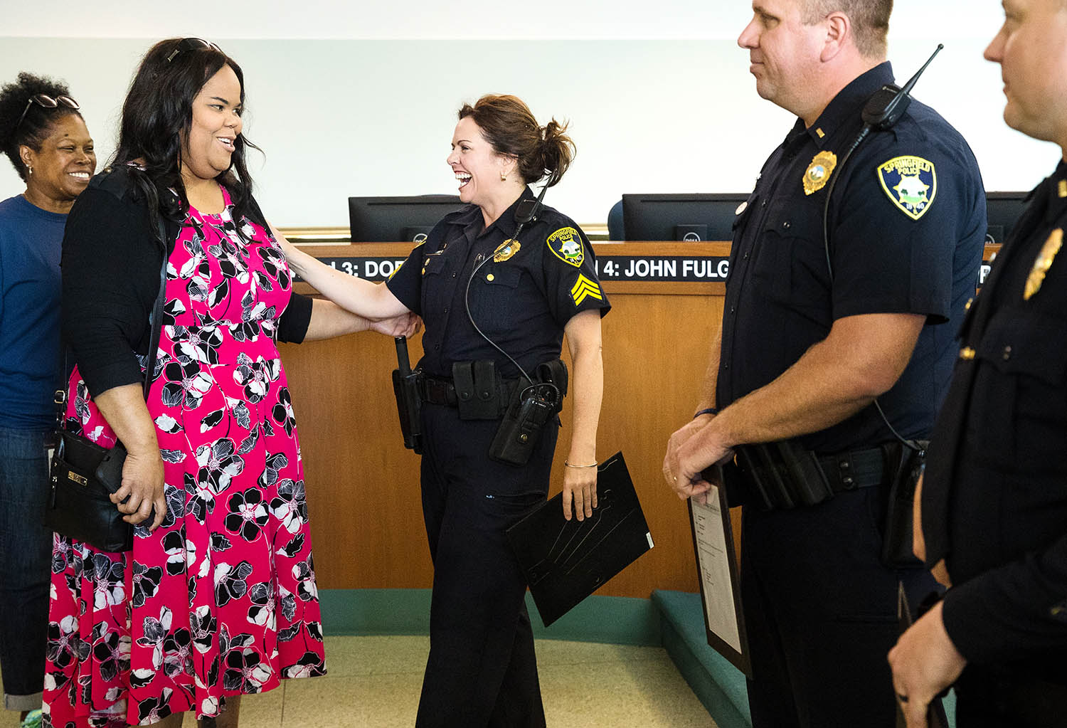 Jacenta Wilson laughs with her best friend and newly promoted Springfield Police Sgt. Amy Strawn after a ceremony where four officers were awarded new ranks in the Springfield City Council chambers Monday, June 20, 2019. [Ted Schurter/The State Journal-Register]